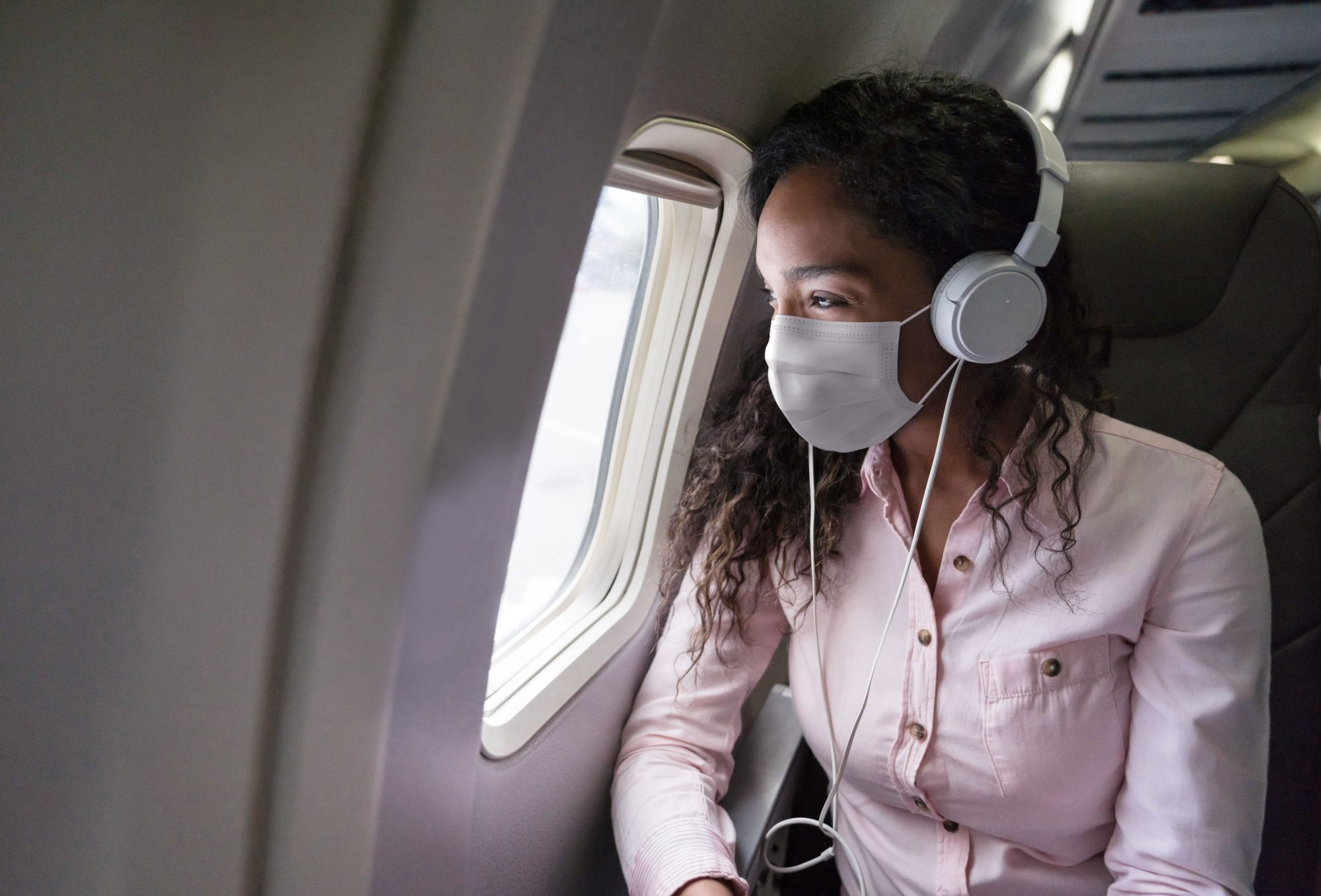 woman wearing face mask on ariplane