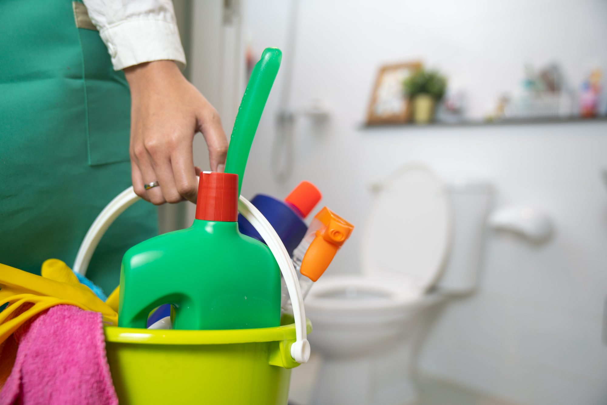 woman holding bucket with cleaning products