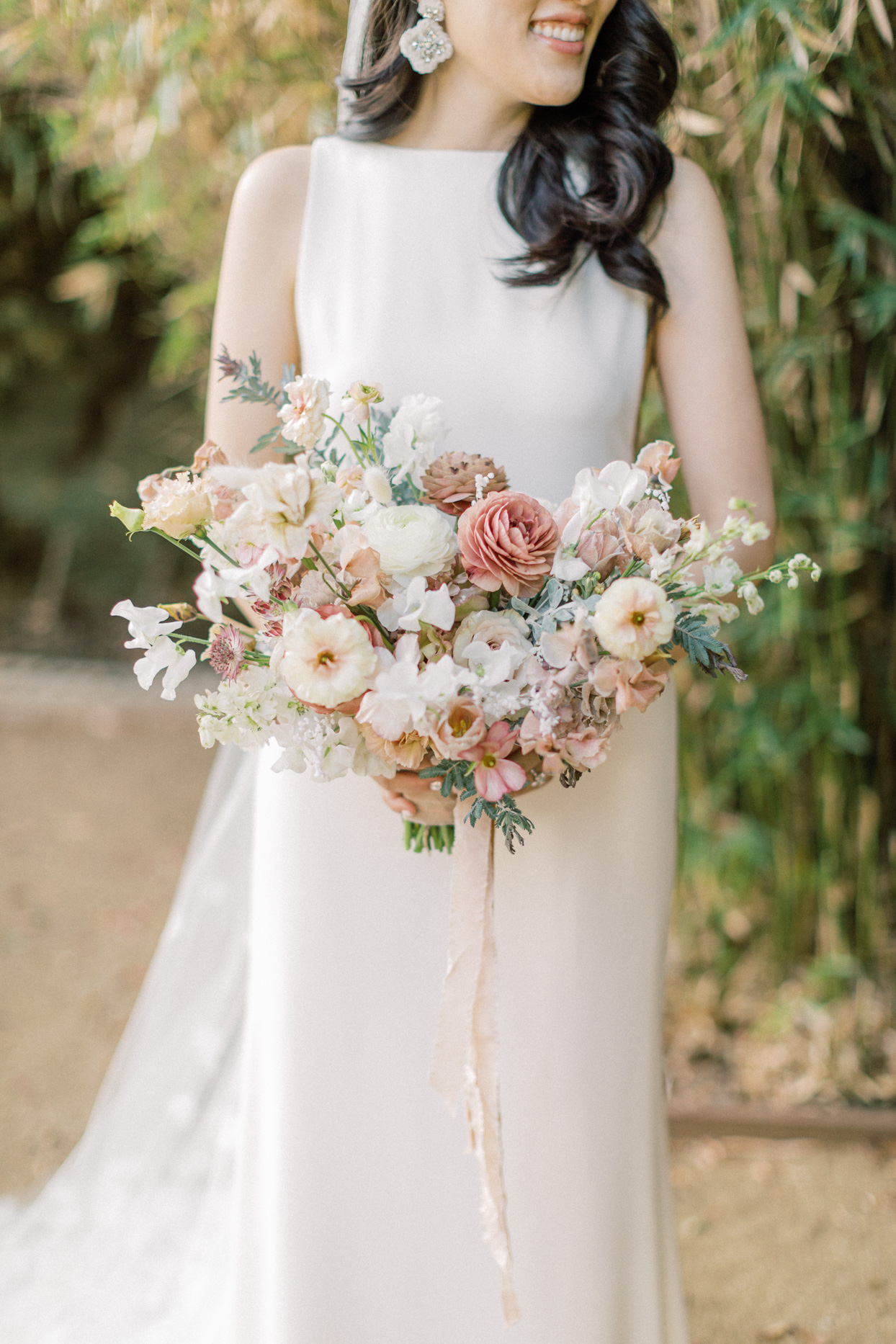Bride holding bouquet with pink accents
