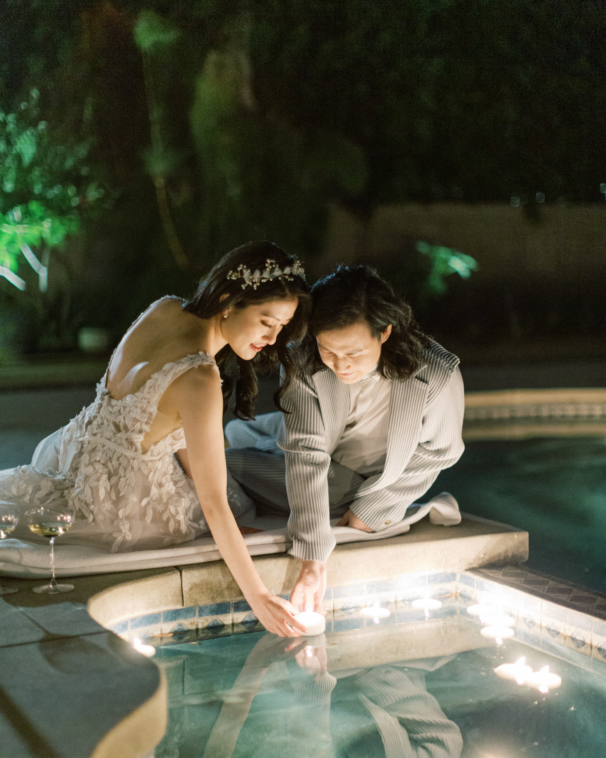 bride and groom placing candle in the water
