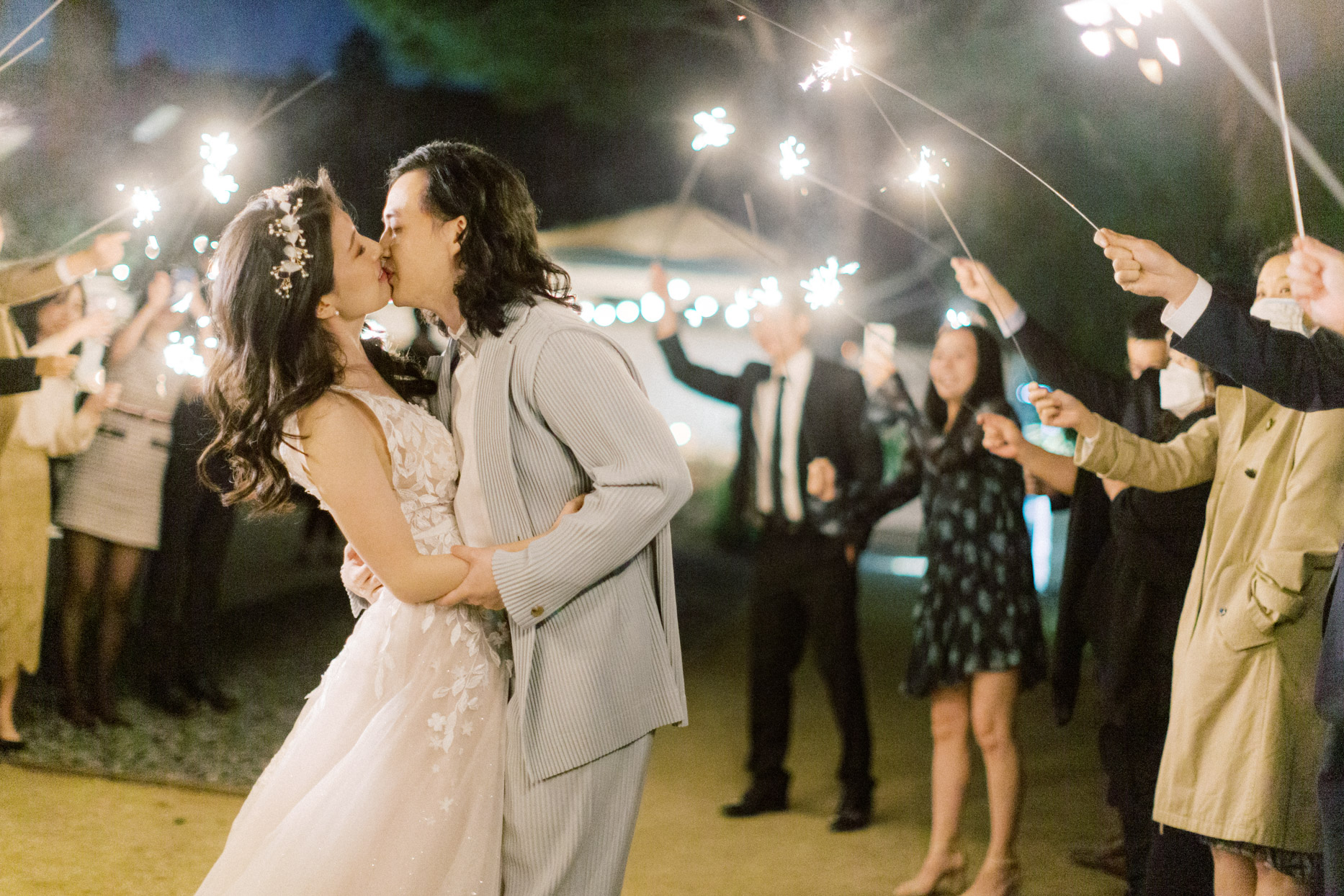 bride and groom under sparklers held by guests