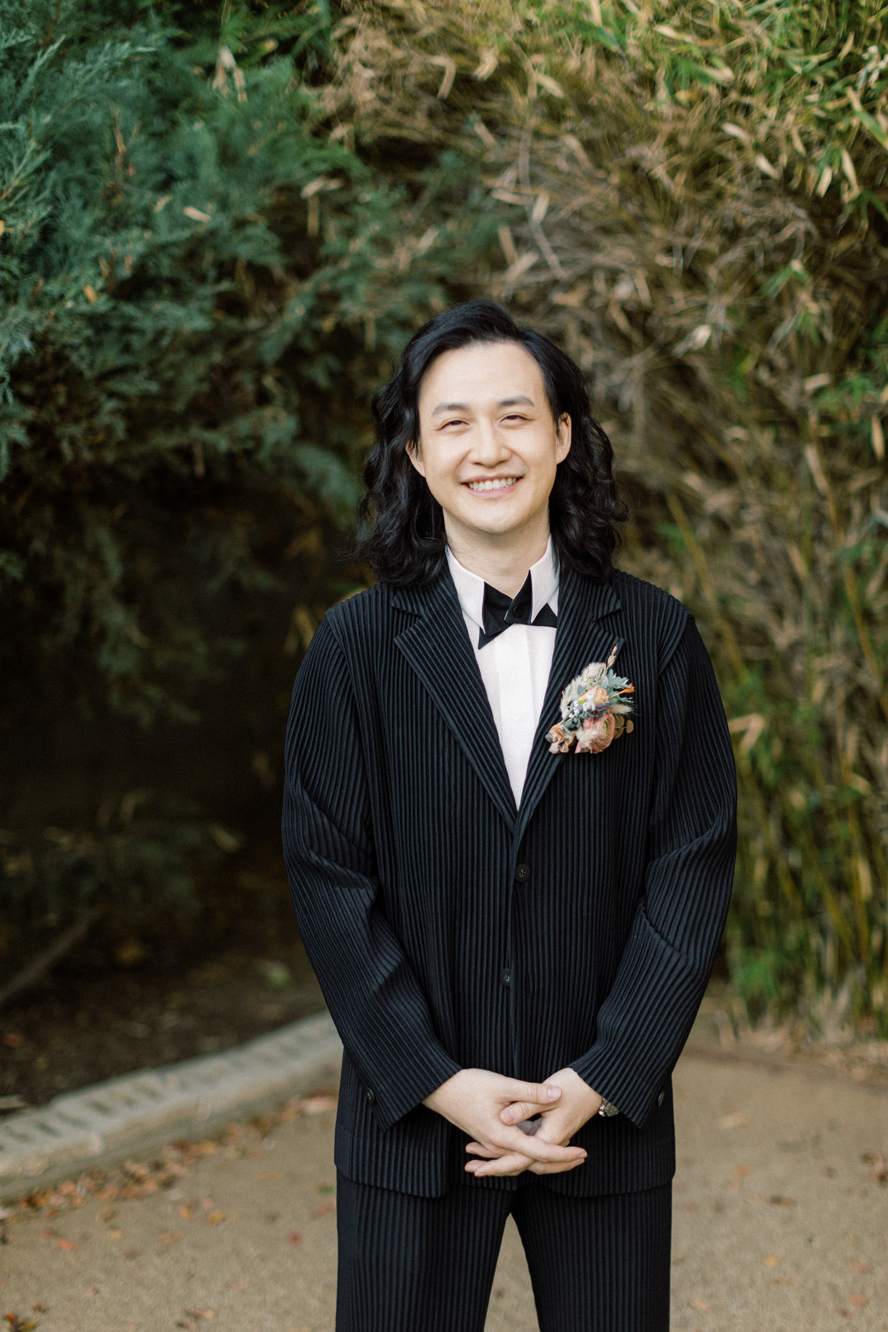 groom in black stripped suit with boutonniere