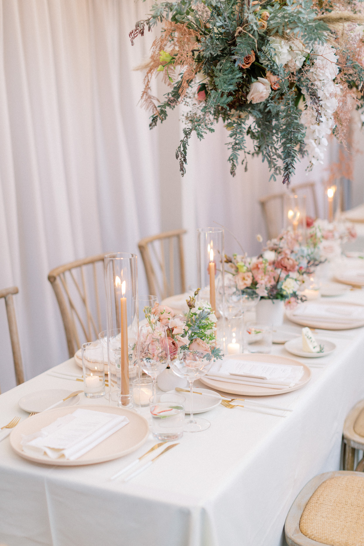 long reception table with blush plates and florals