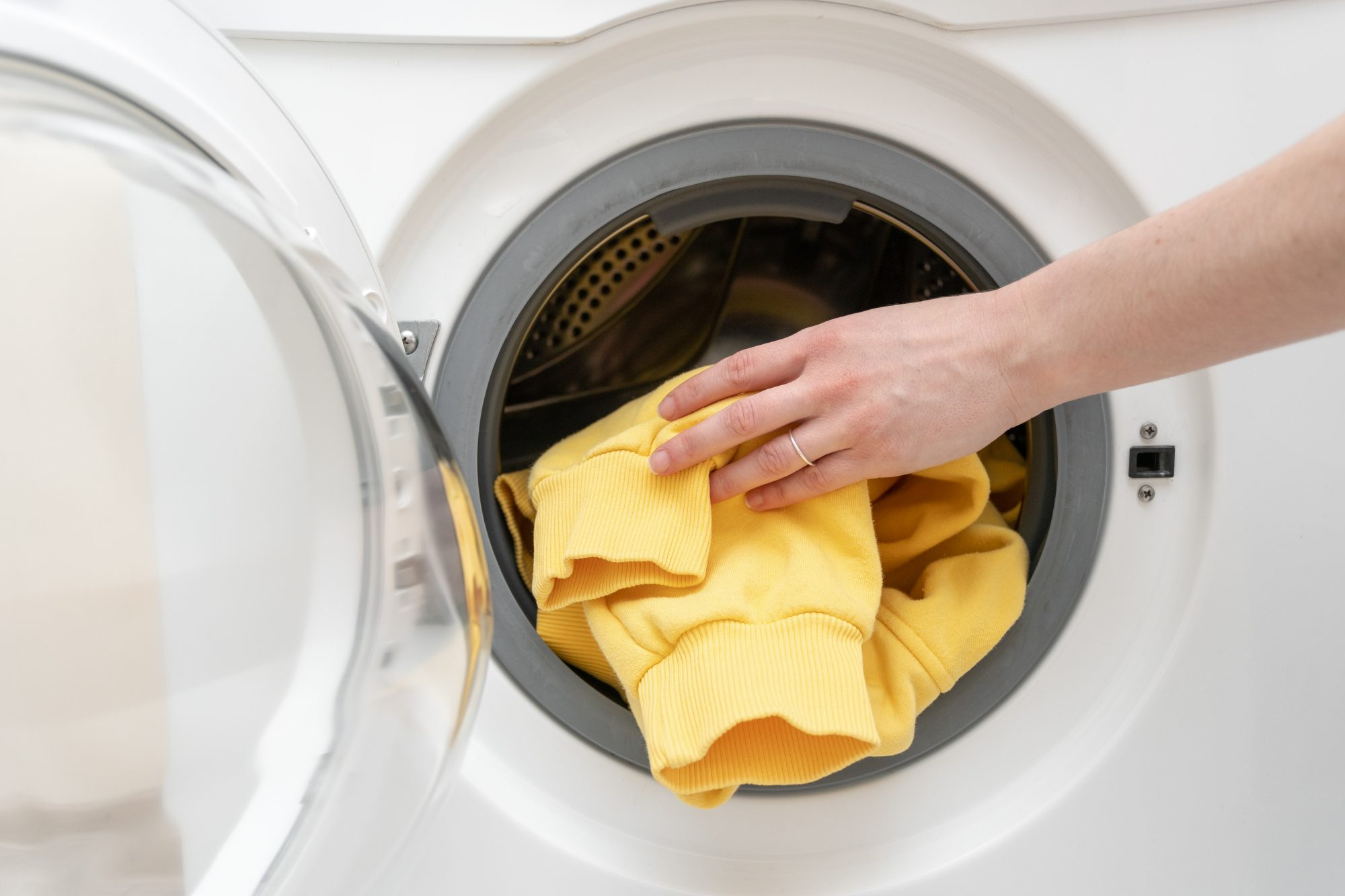 pulling yellow shirt from dryer