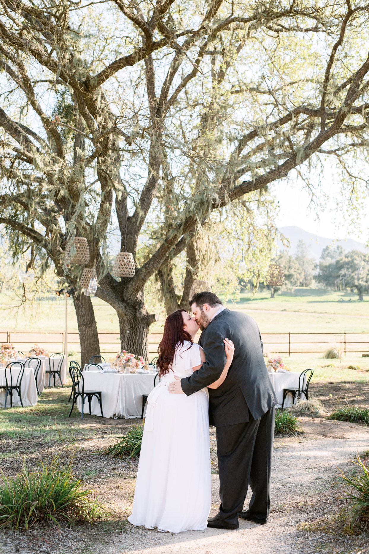 bride and groom kissing in front of outdoor rehearsal dinner space