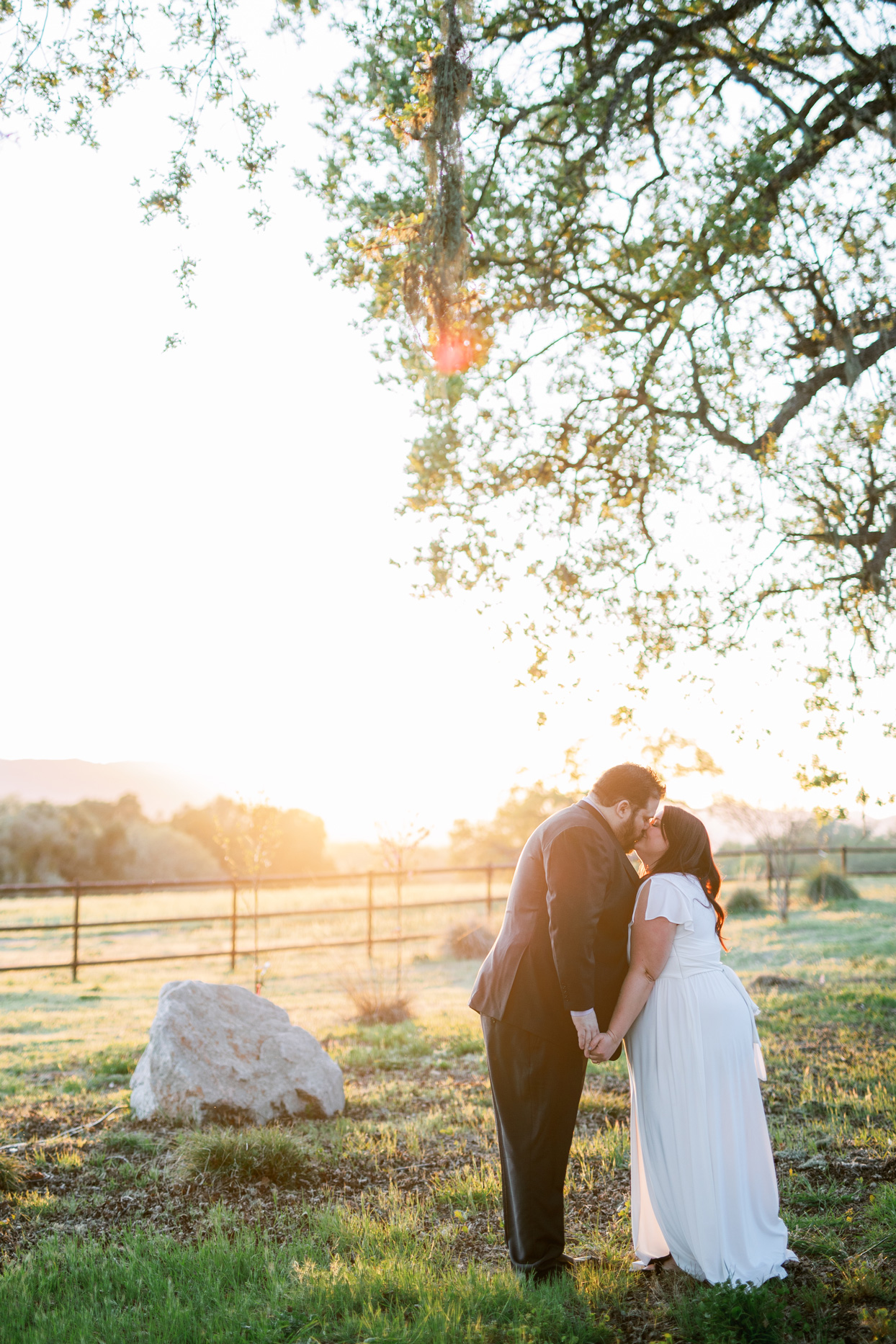 bride and groom kissing with california ranch backdrop at sunset