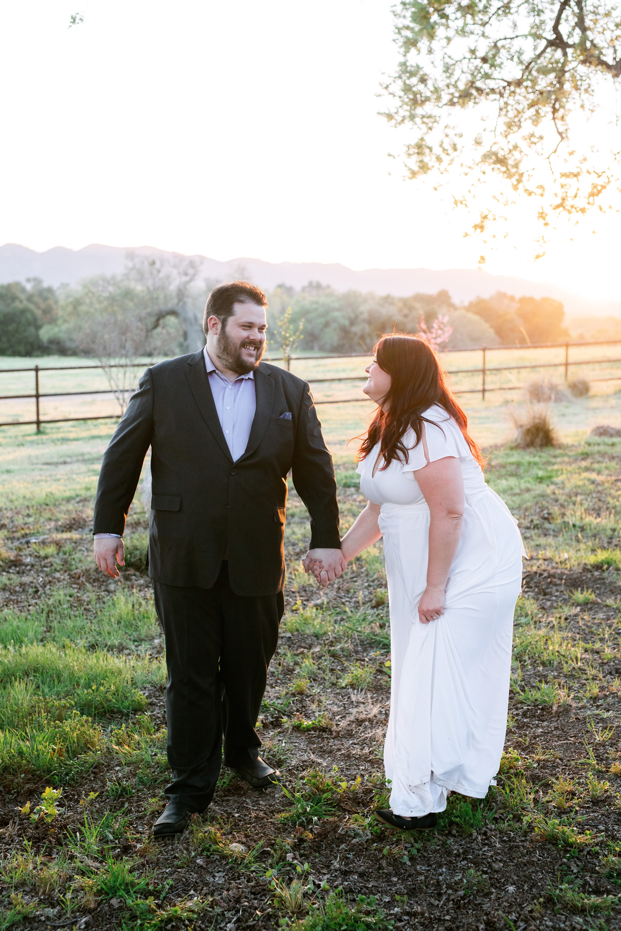 bride and groom holding hands california ranch backdrop at sunset