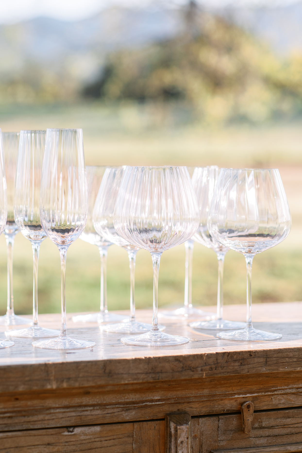 rehearsal dinner glassware atop outdoor wood bar