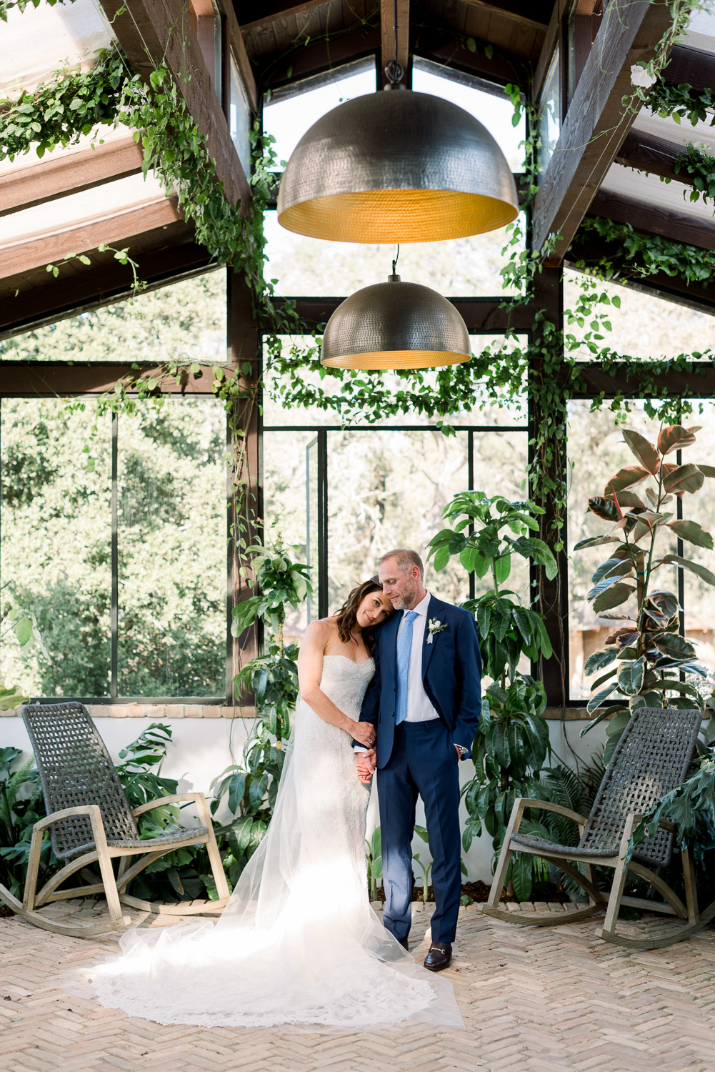 bride and groom at venue with greenery