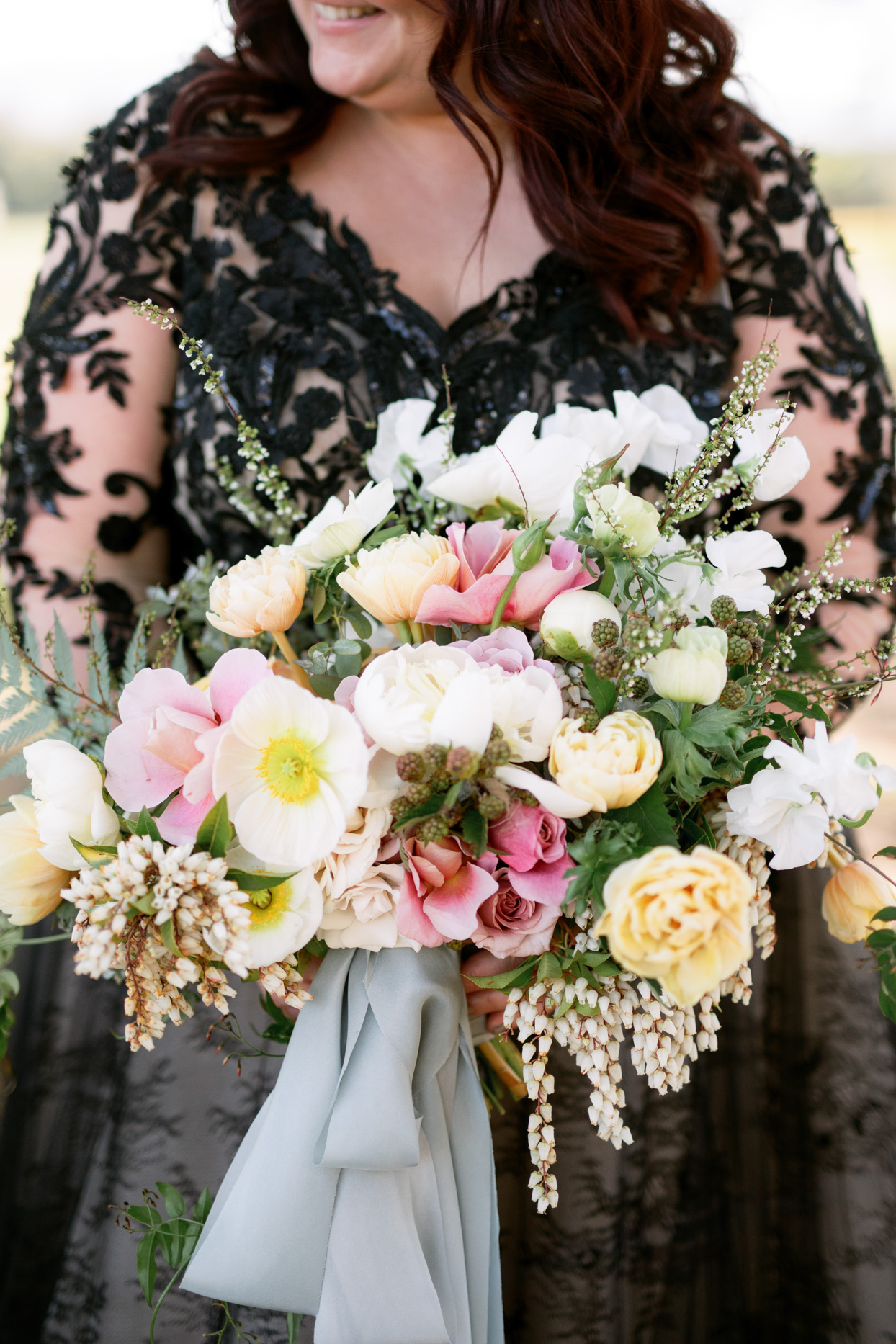 Bride holding bouquet with pink and yellow flowers