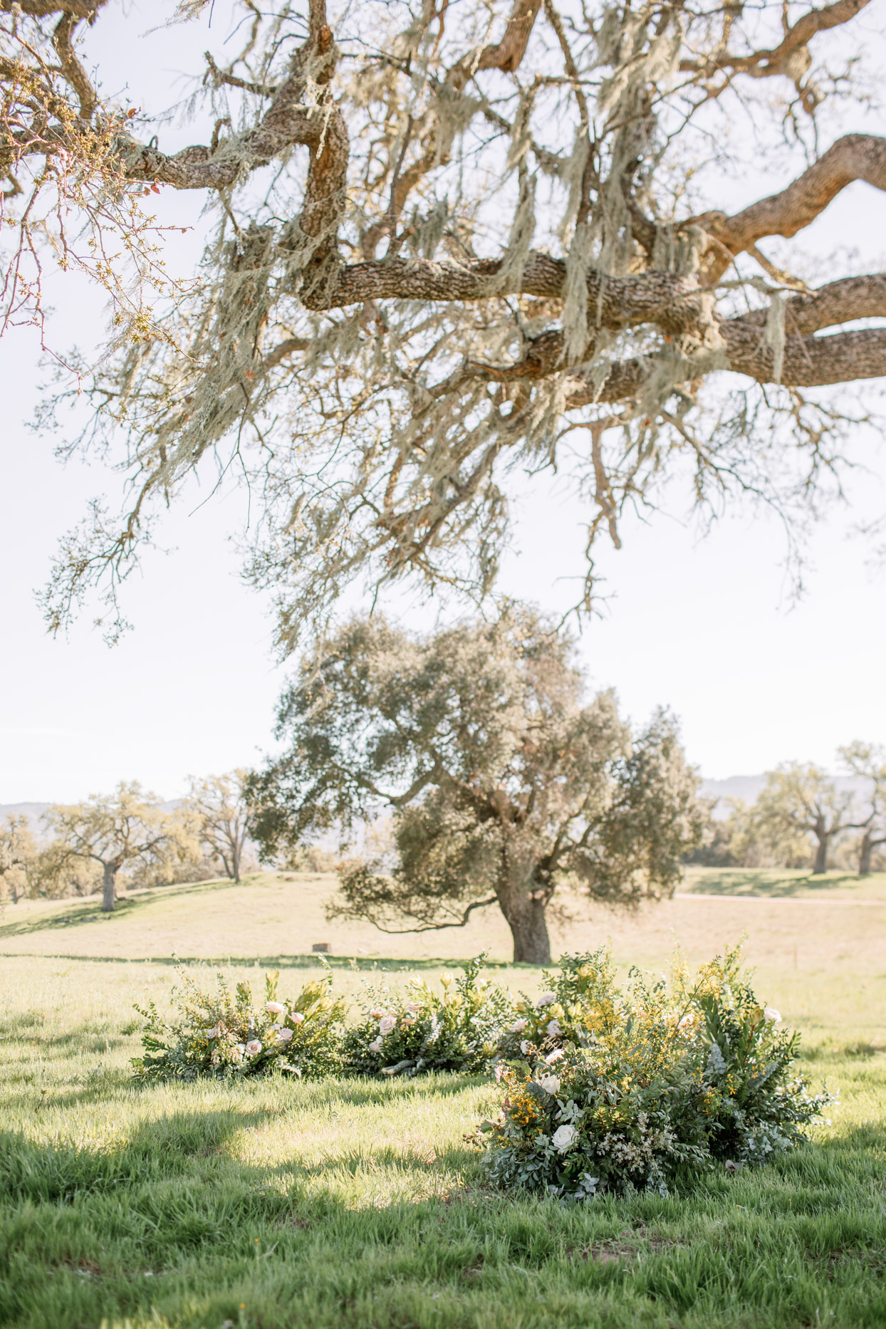 wedding ceremony ground arch with flowers and greenery