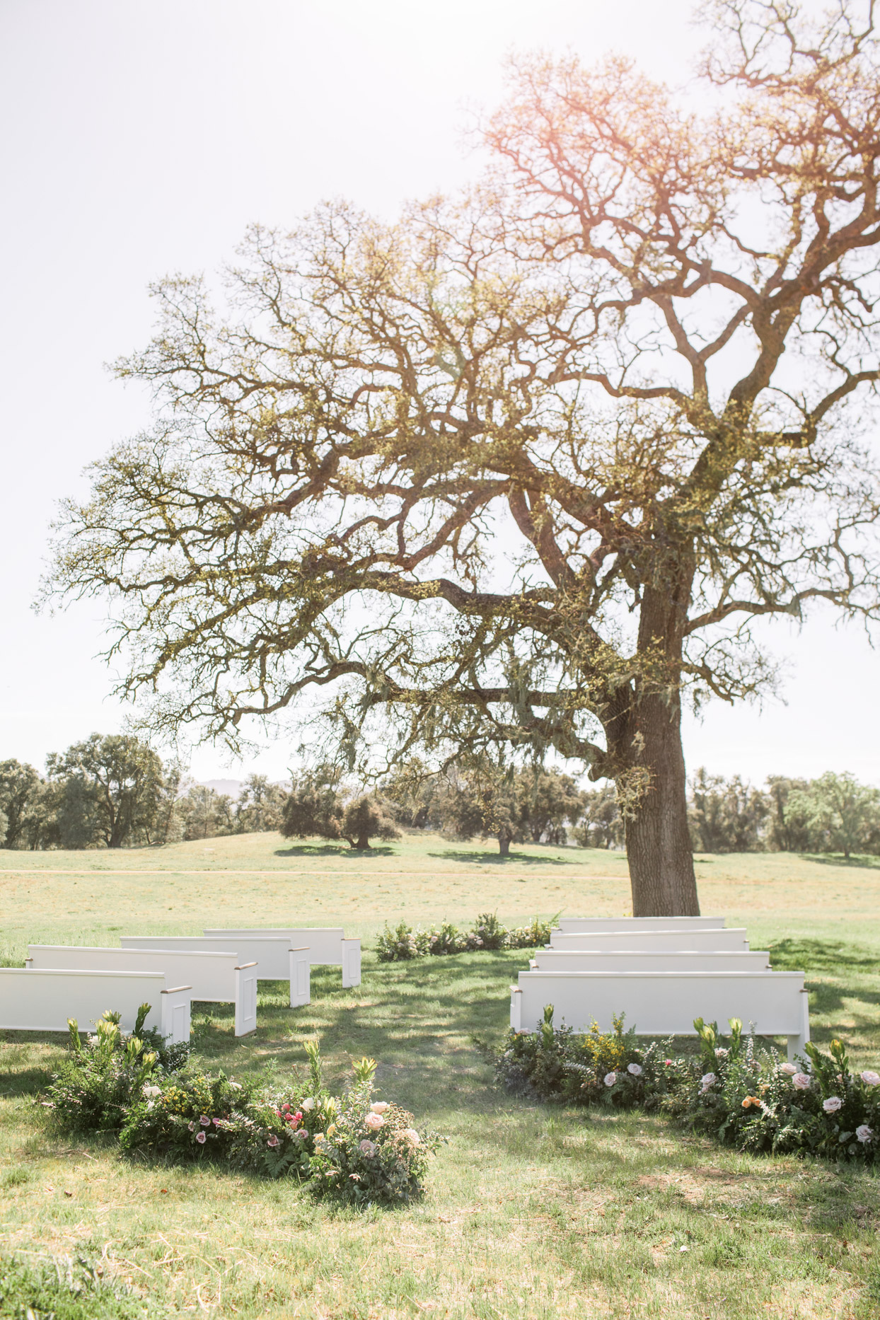 ceremony set with white pews on the grass