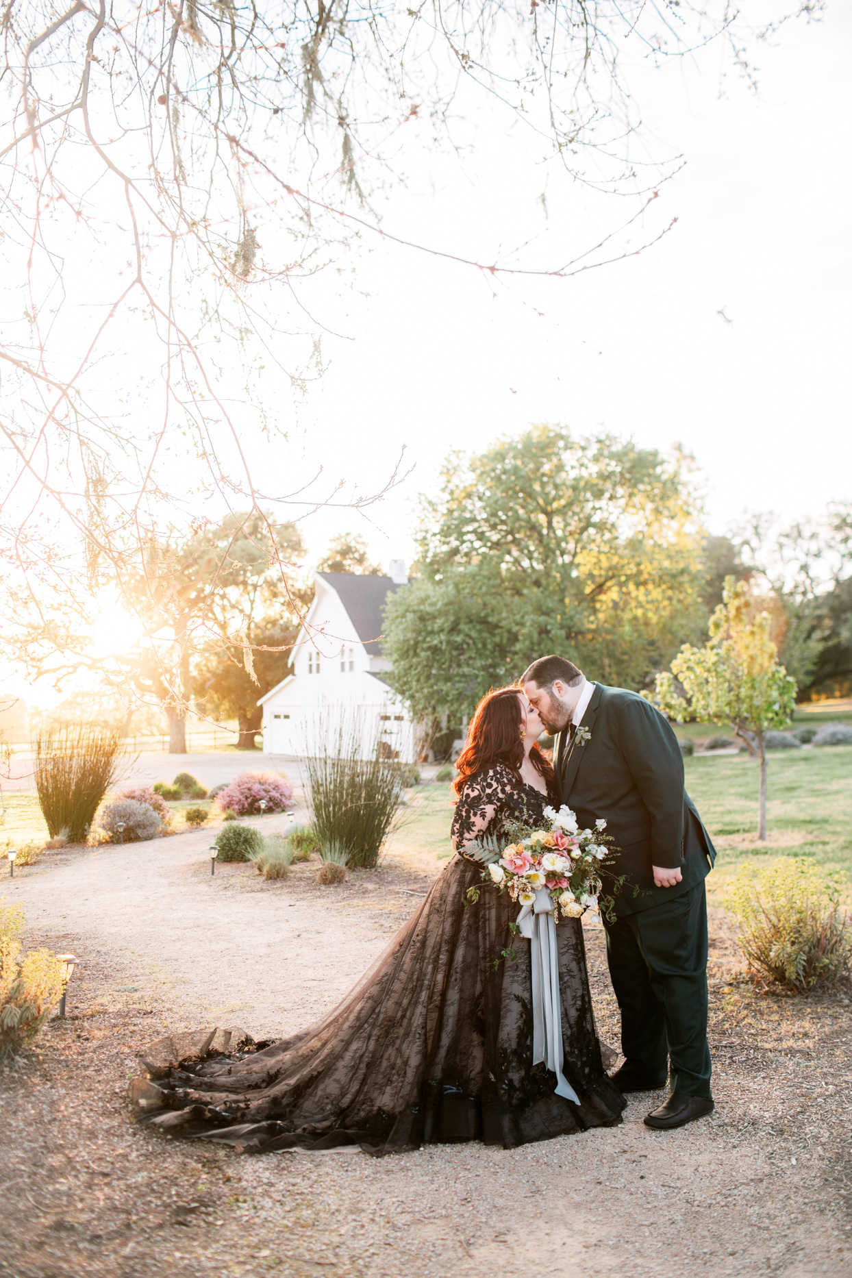 bride and groom kissing on gravel path