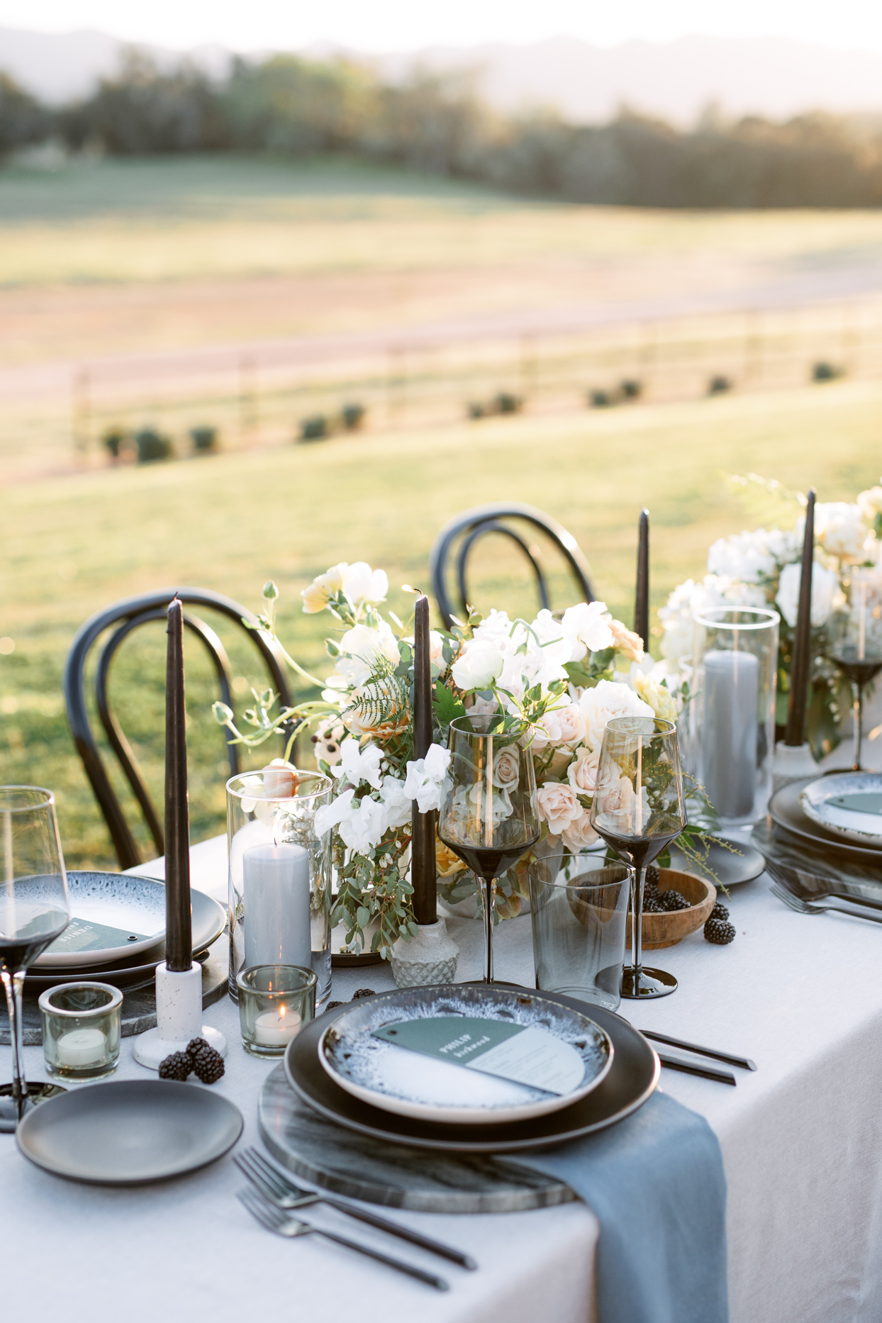 table setting with tall black candlesticks accented with grey napkins and plates