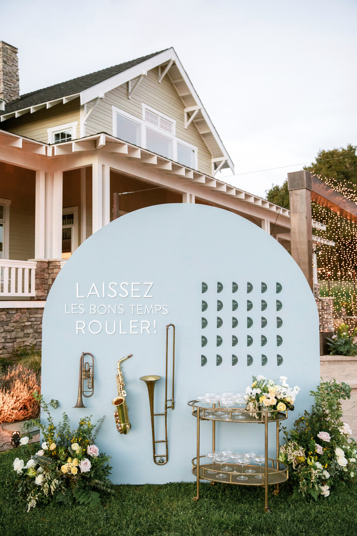 seating chart board with brass instruments, flowers and cocktail table