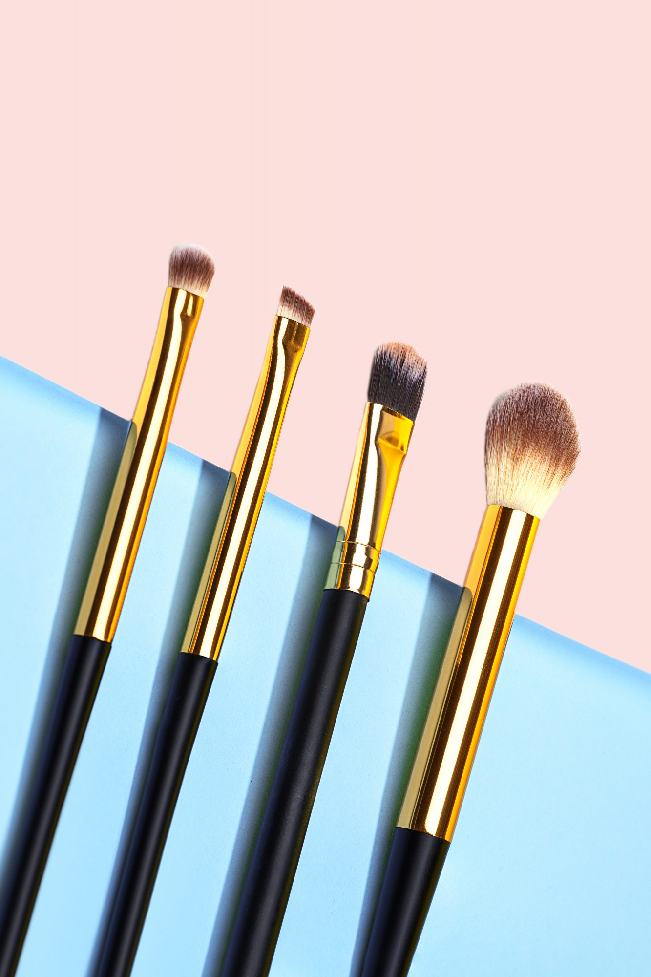 assortment of makeup brushes on blue and pink background