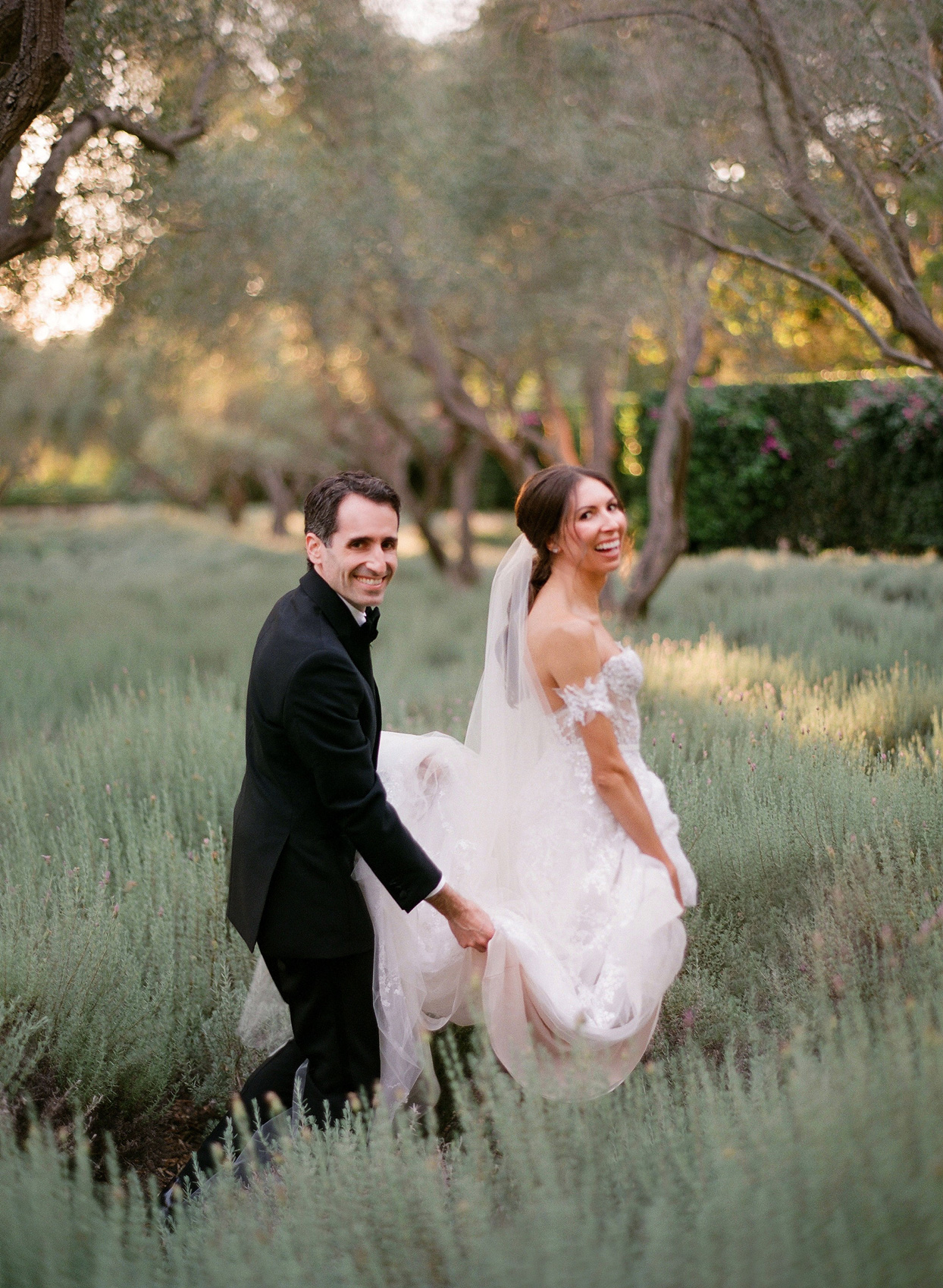 groom carrying brides train in field