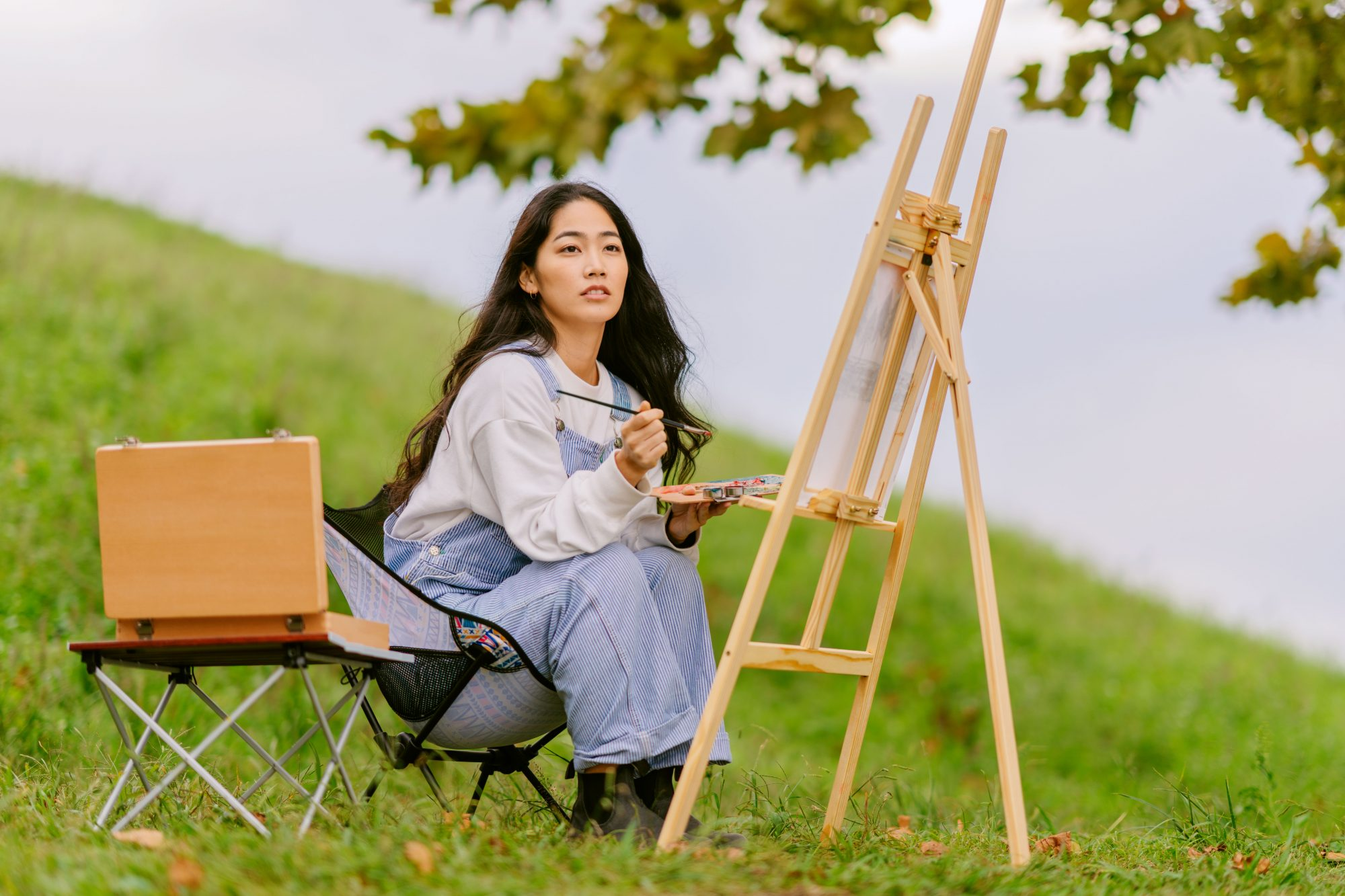 artist painting on canvas outdoors in field