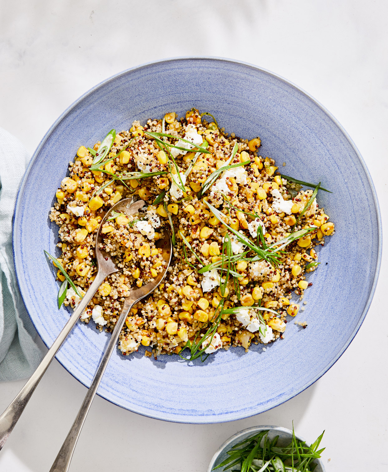 quinoa with caramelized corn and scallions served in a blue bowl