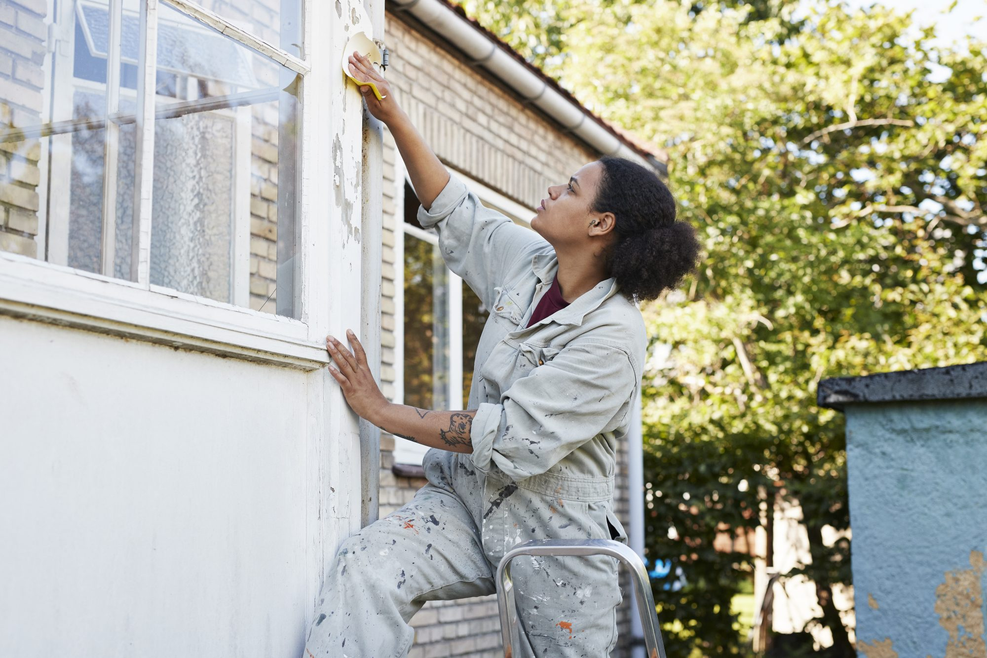 woman sanding exterior of home