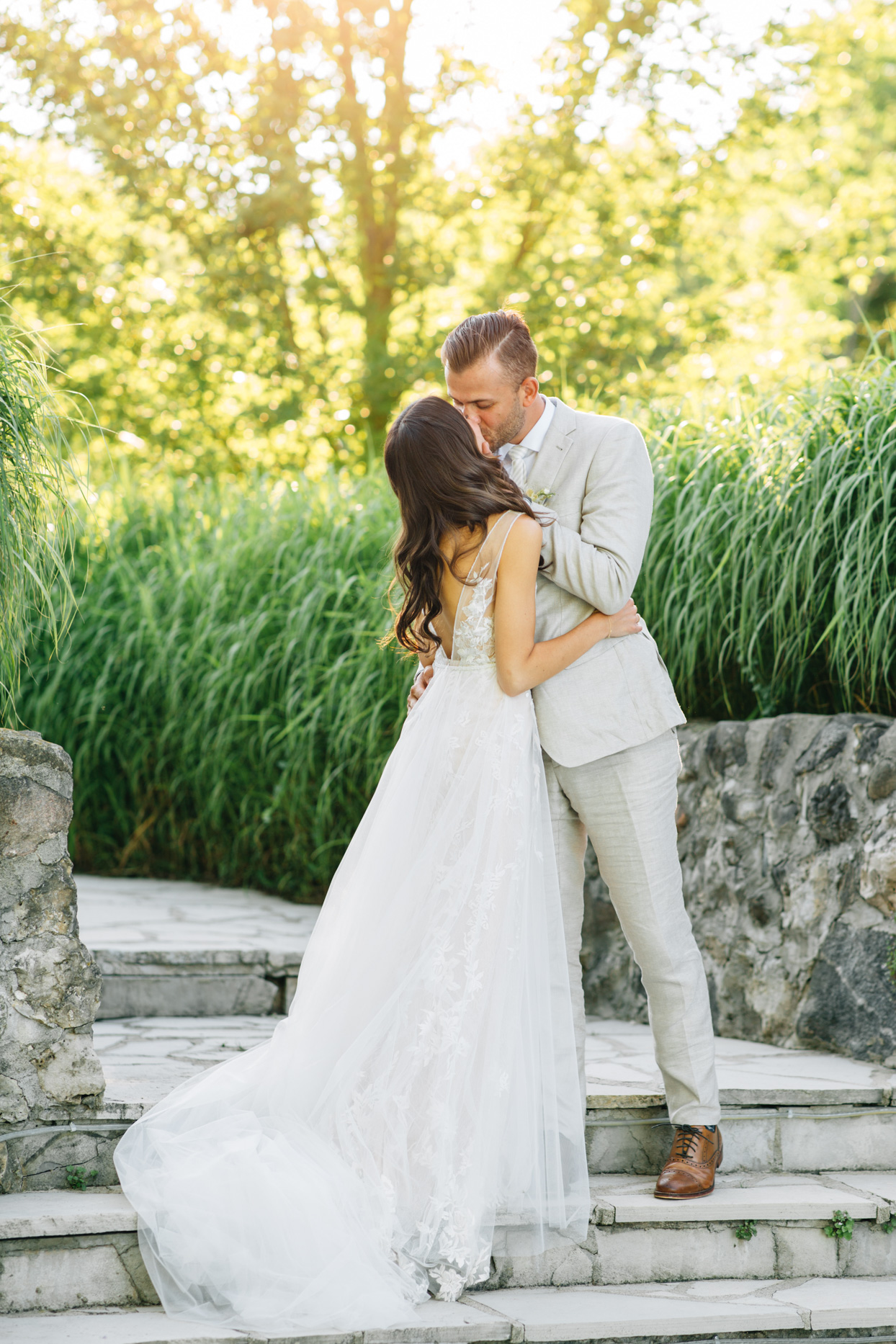 bride and groom kissing on stone steps