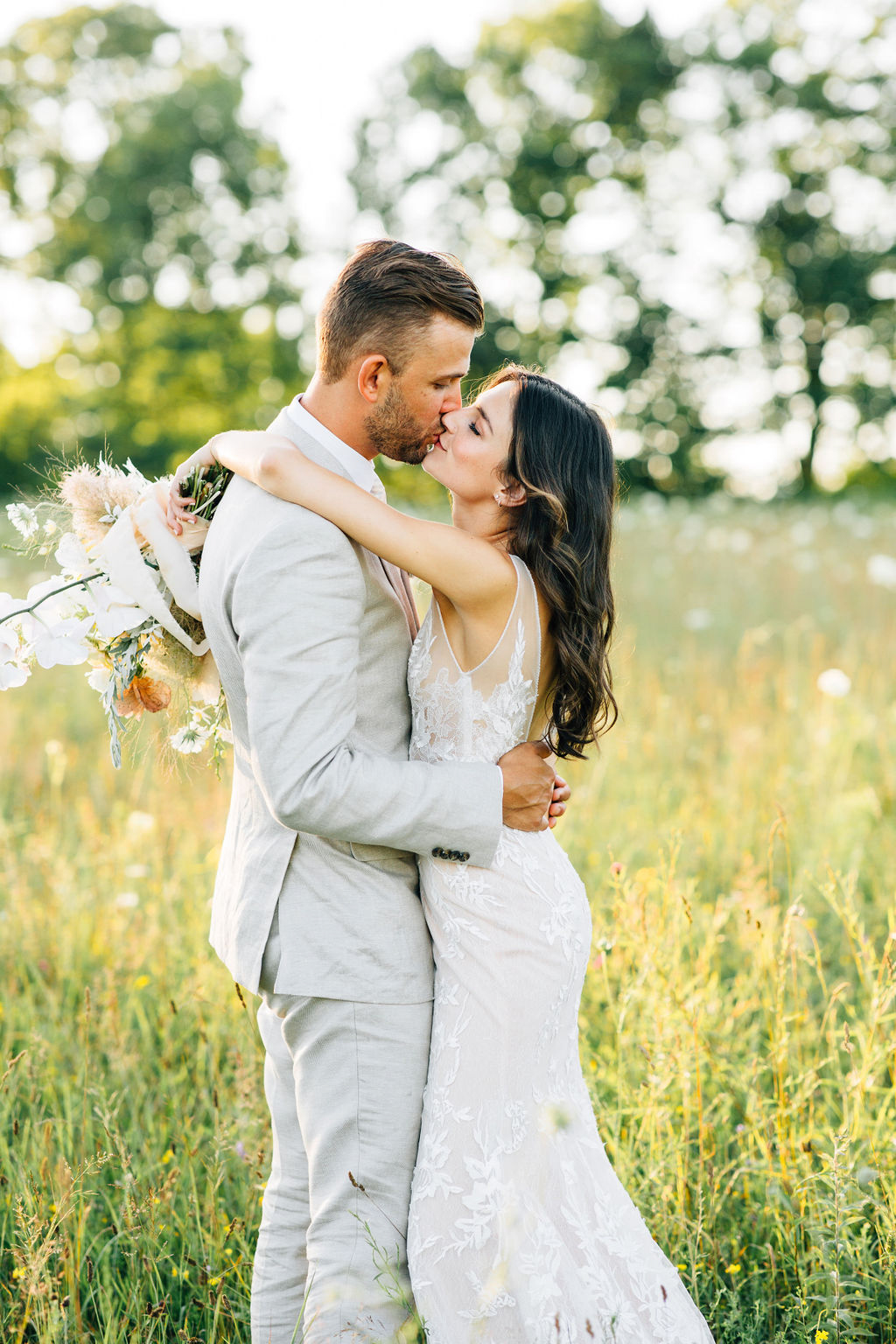 close up of bride and groom kissing in field