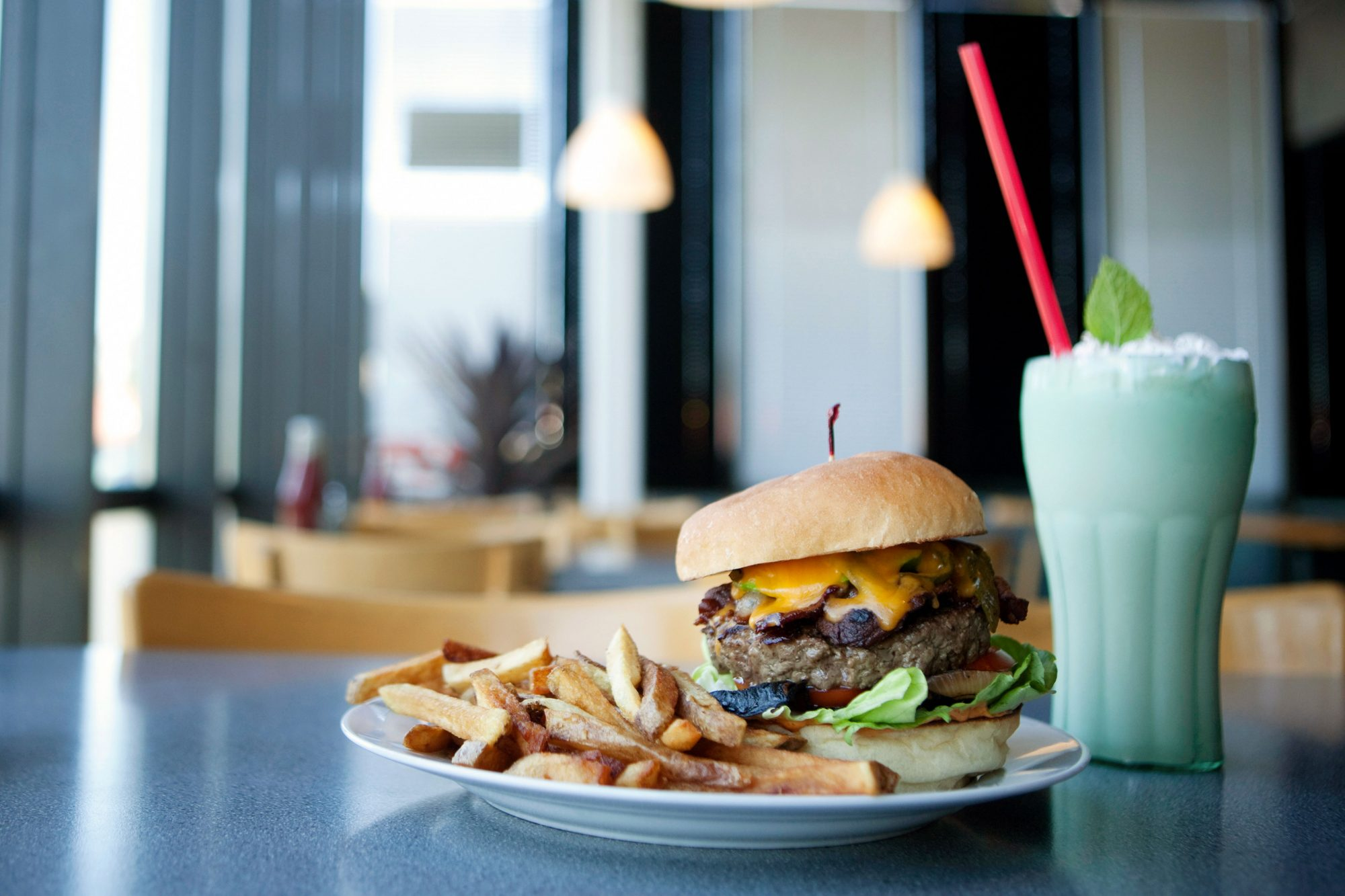 cheeseburger with fries and milkshake on table