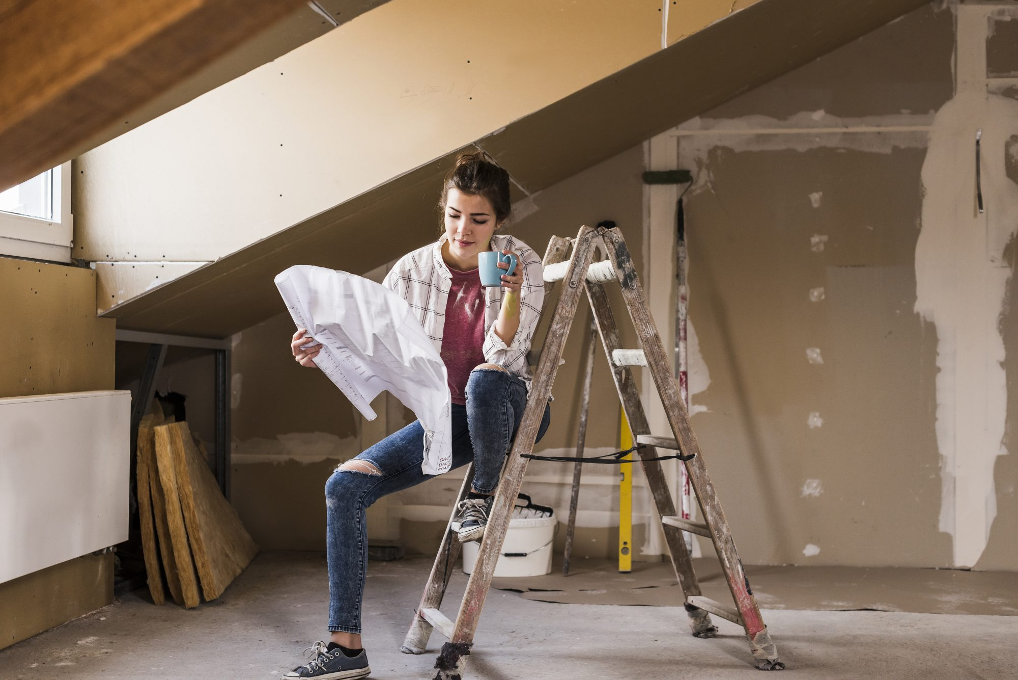 Young woman renovating her new home, holding construction plan