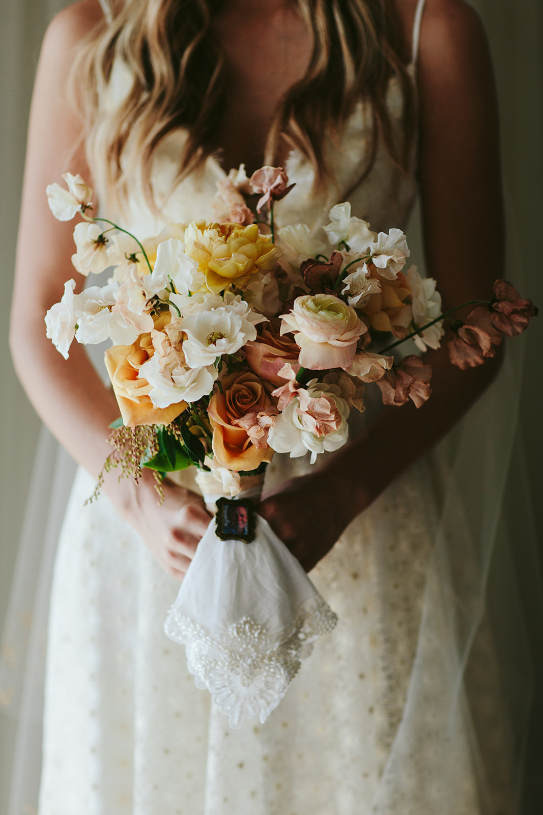 bride holding pink, orange, and yellow floral bouquet