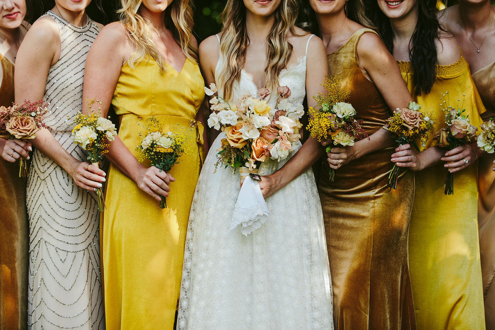 bridesmaids in assorted gold, mustard and beige dresses