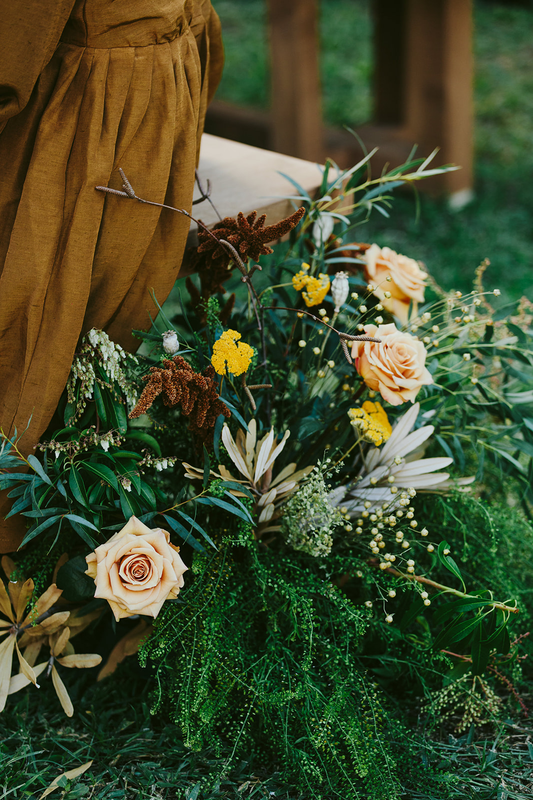 lush greenery and fall colored florals at wedding ceremony