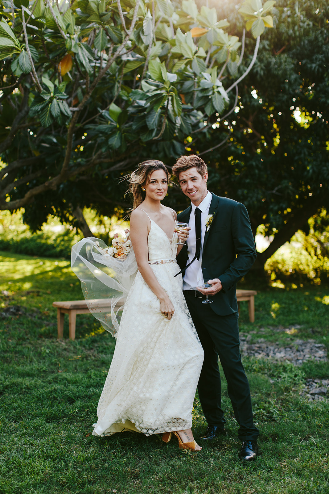 wedding couple portrait holding champagne outdoors