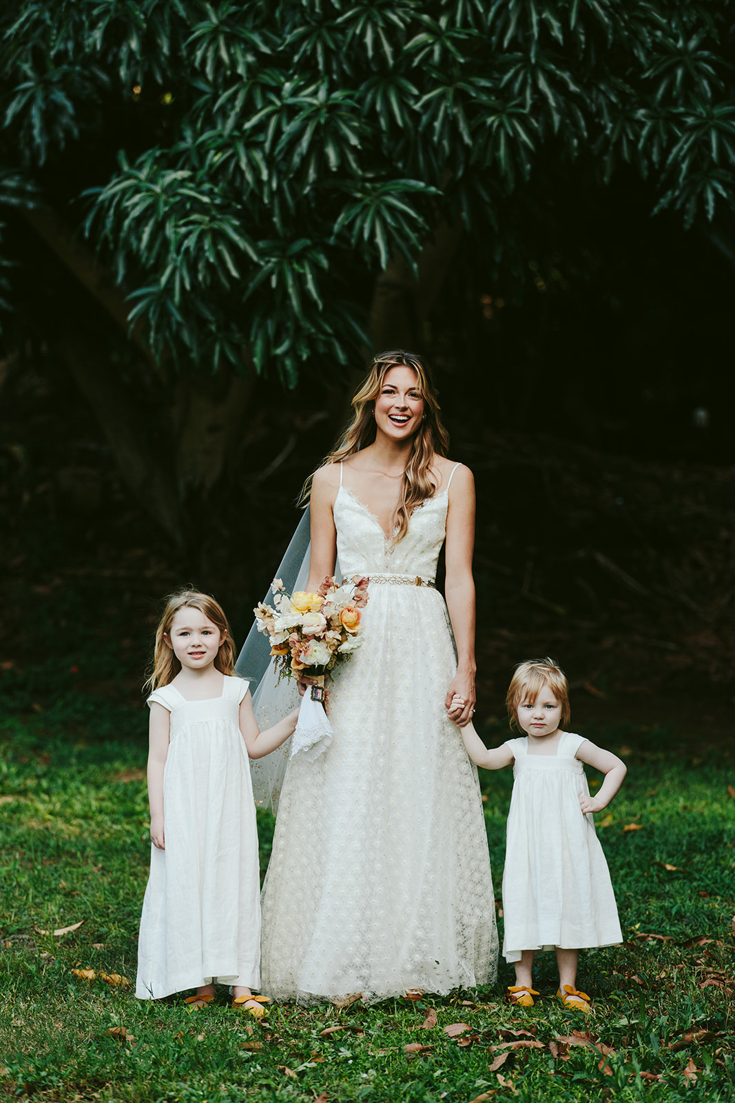 bride smiling while holding hands with wedding flower girls