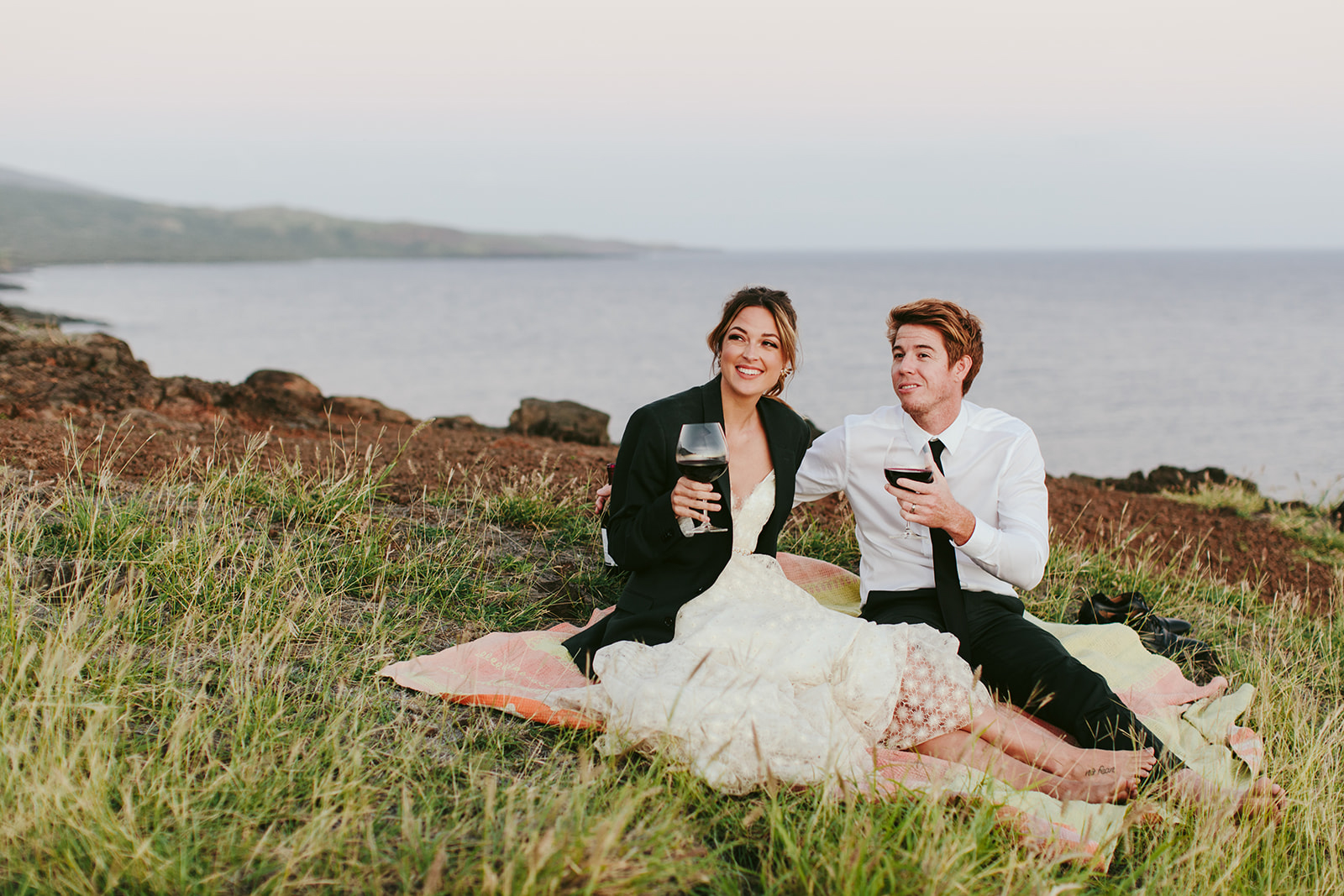 couple sitting on grass for wedding picnic