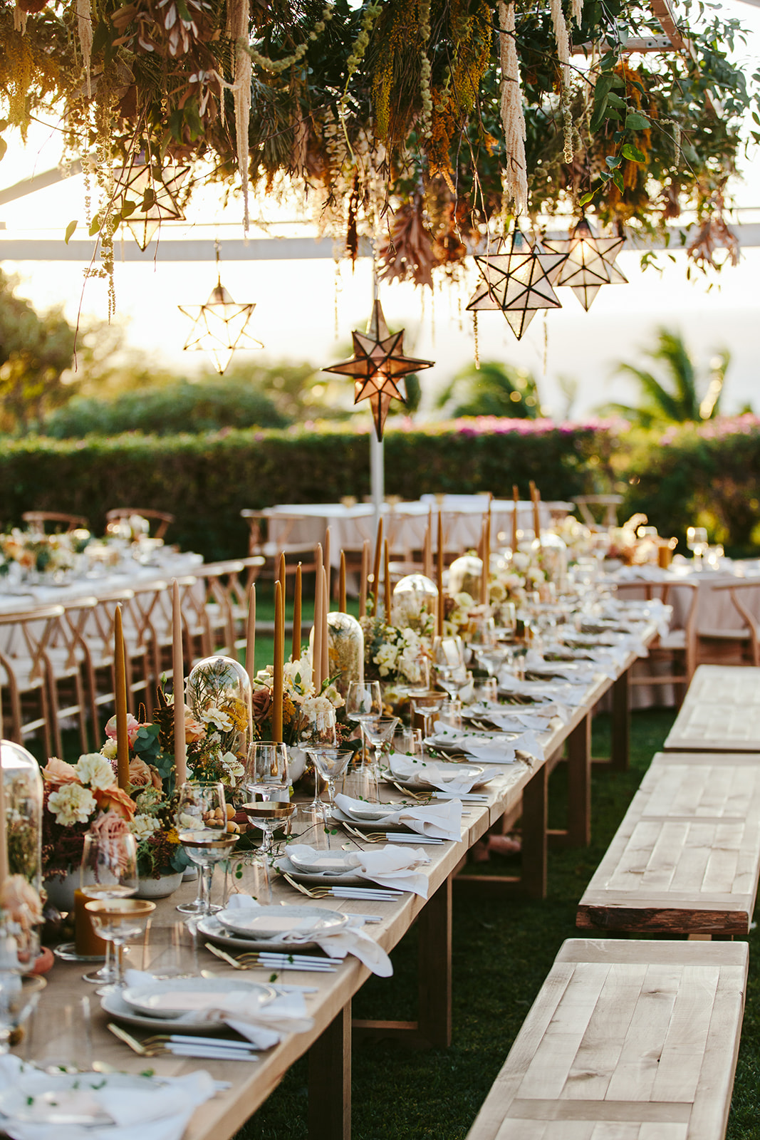 long wooden reception tables with candles, flowers, and hanging stars