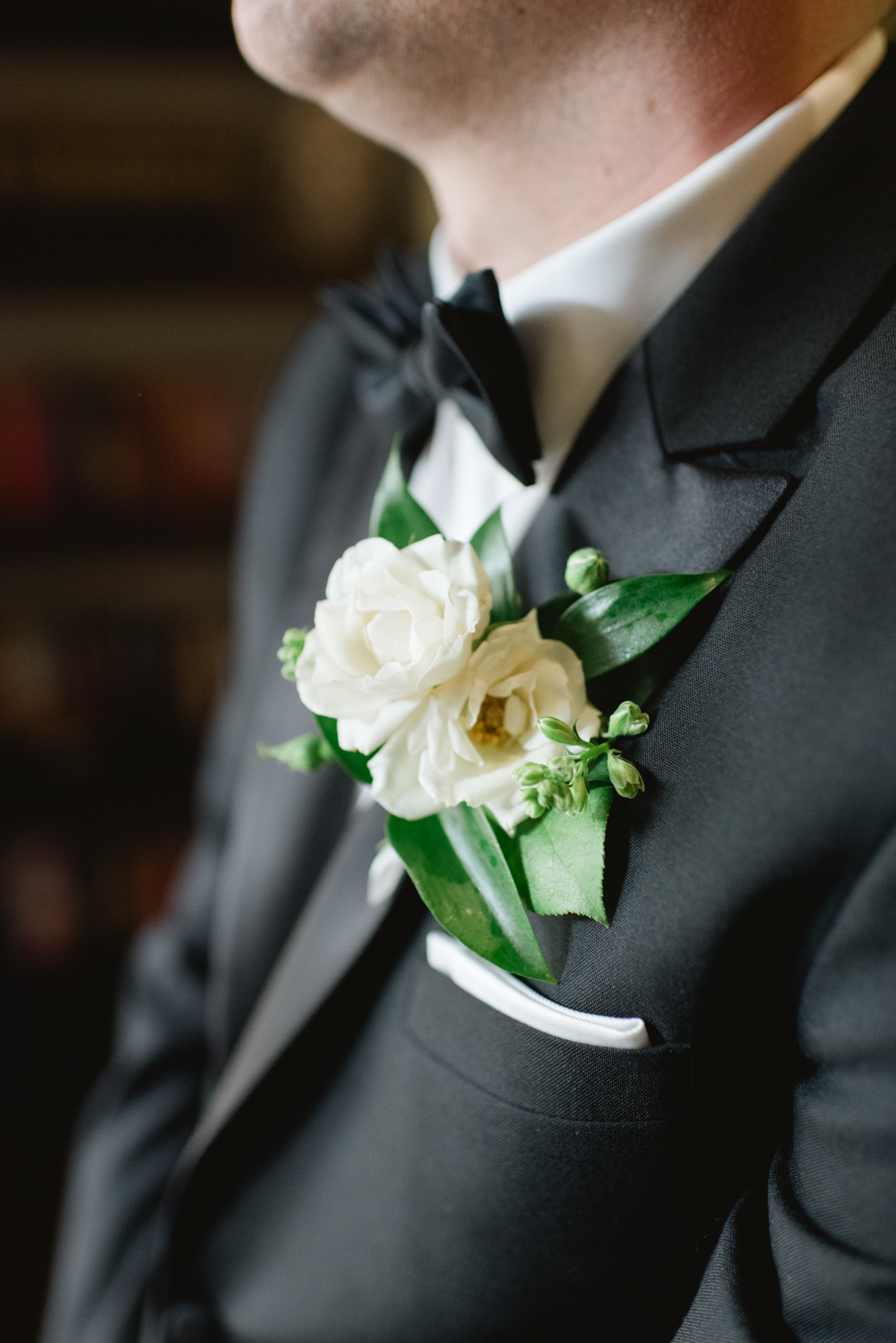 white boutonniere on groom's black suit