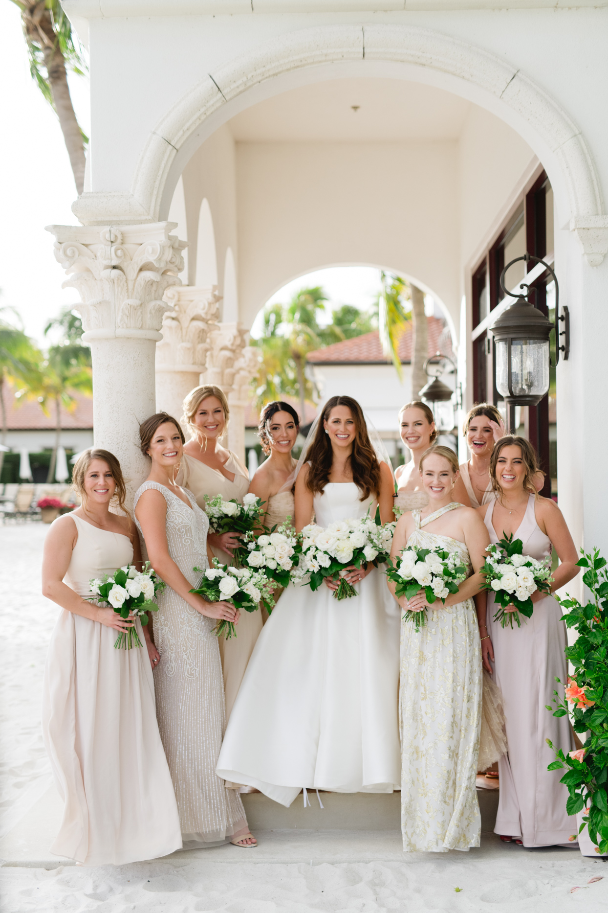 bride in white with bridesmaids in gold and pink