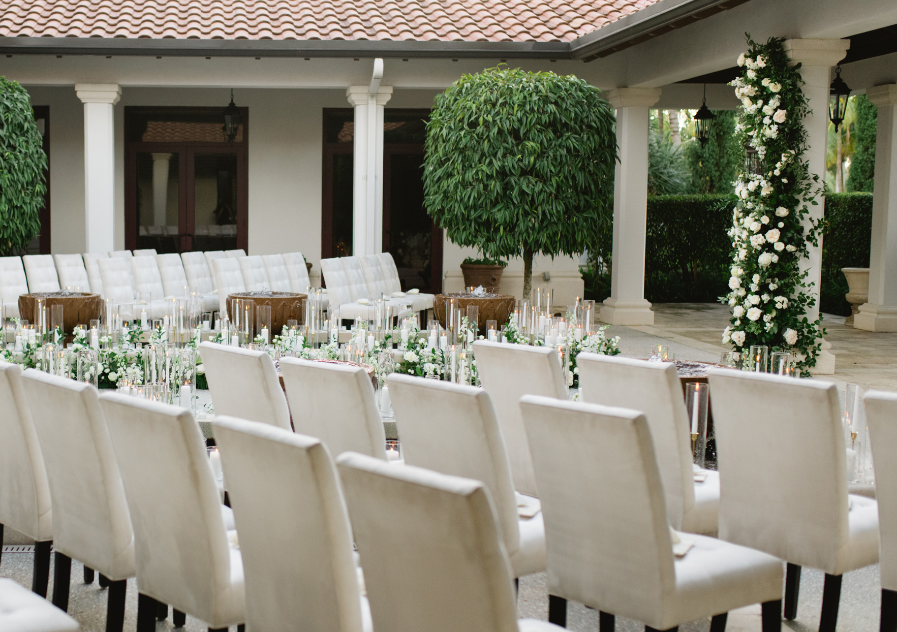 outdoor wedding ceremony with elegant white chairs, candles, and florals
