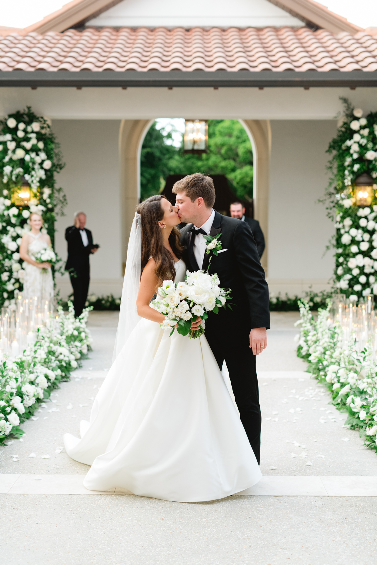 wedding couple kissing on aisle with florals and candles