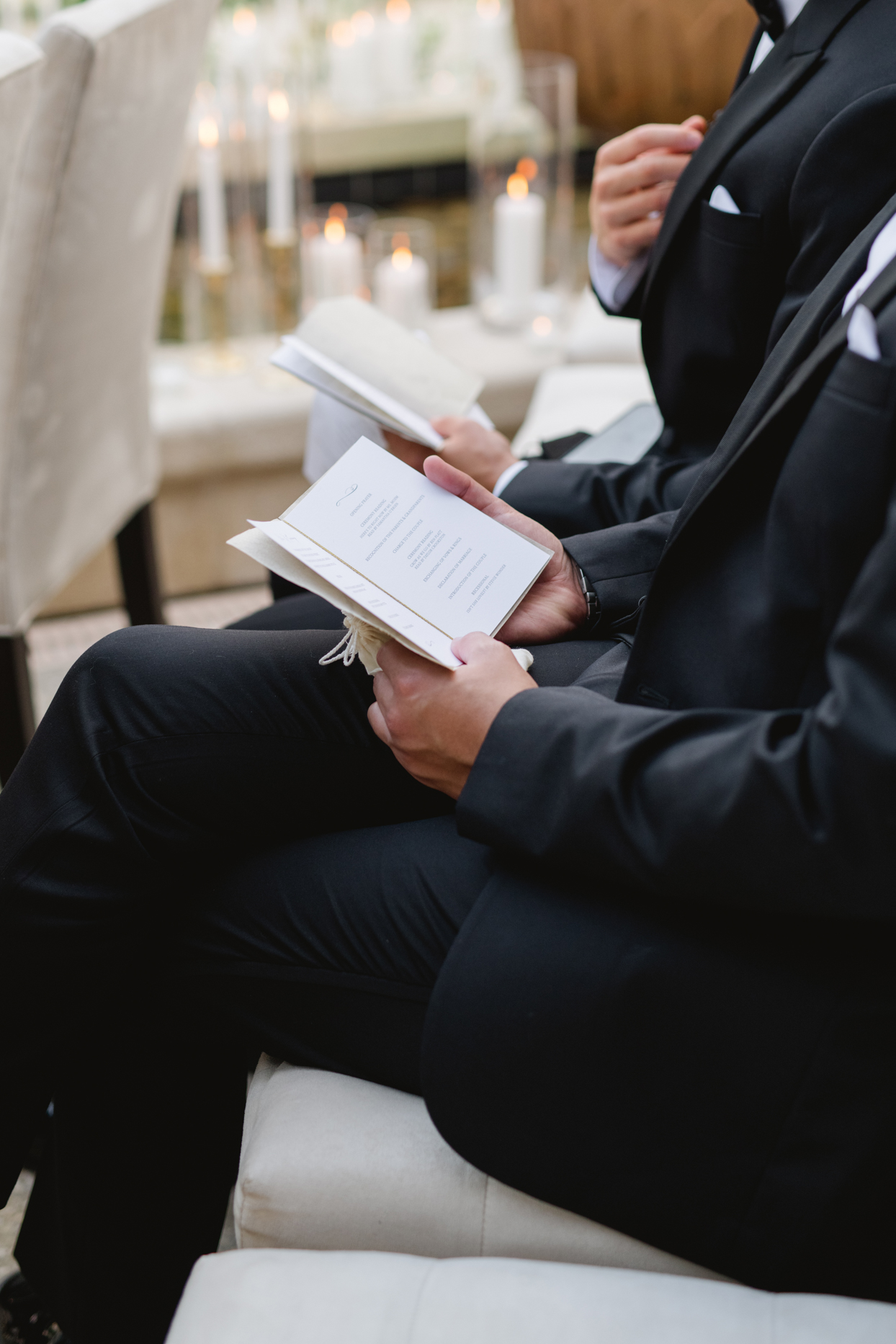 guests in suits holding wedding programs