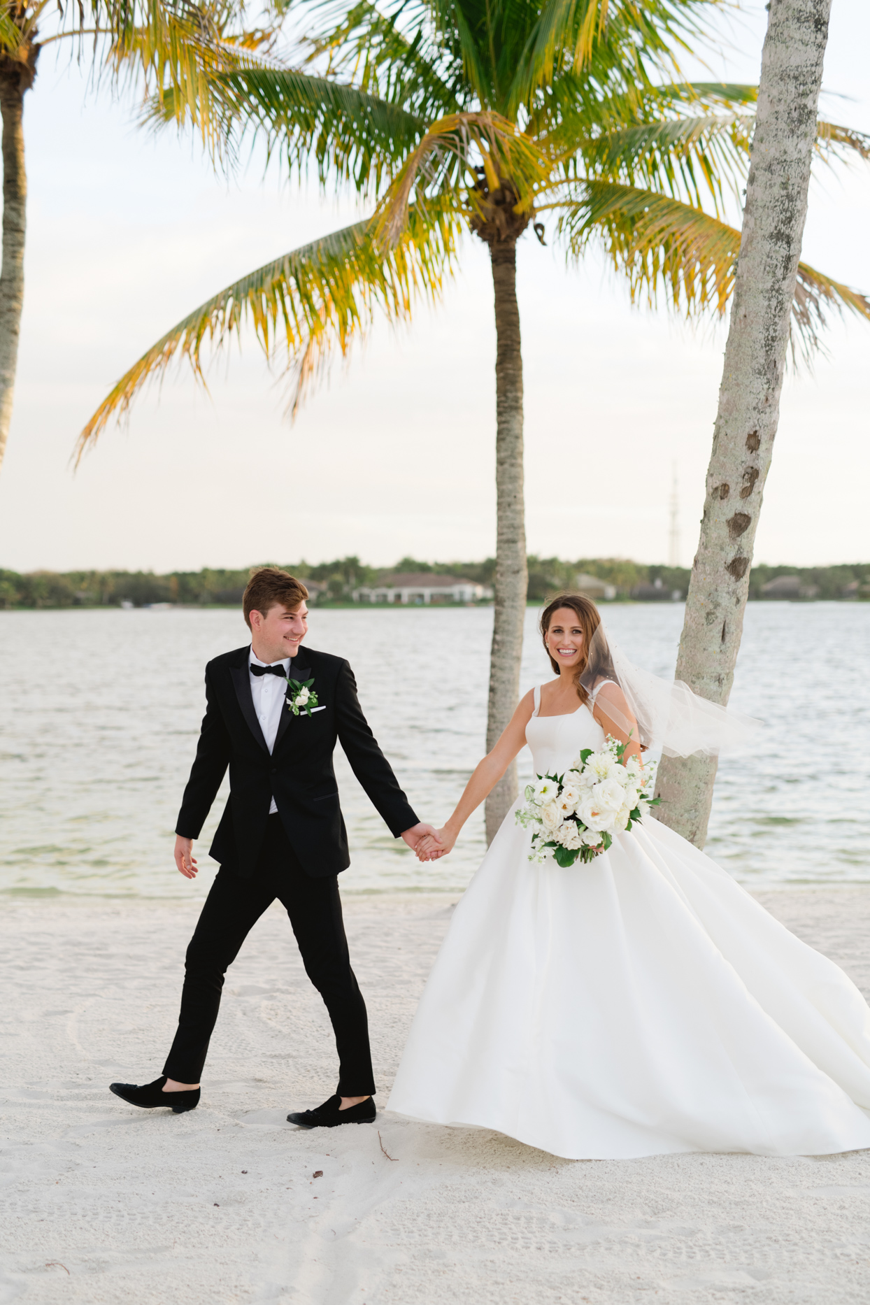 couple walking along beach with palm trees behind