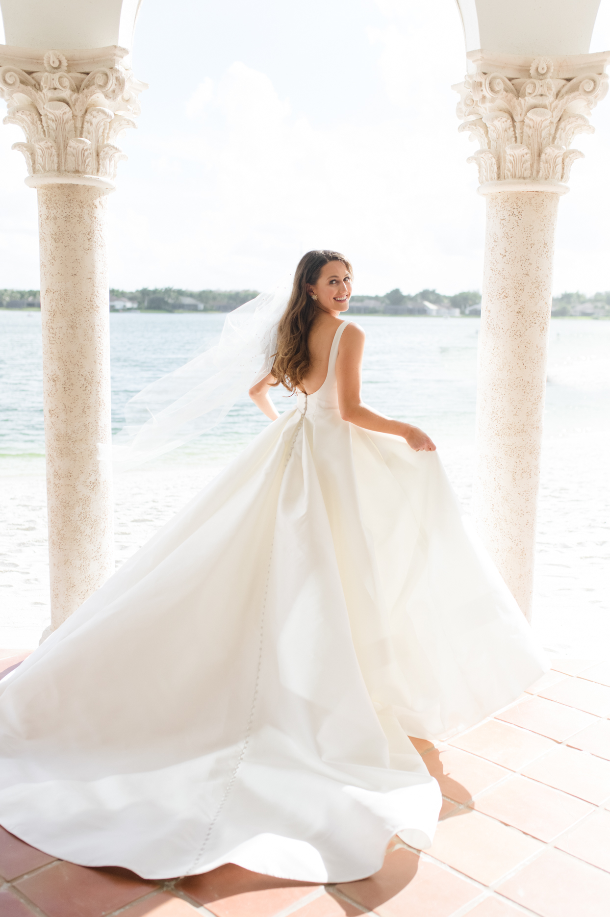 bride in flowing white wedding dress by the water
