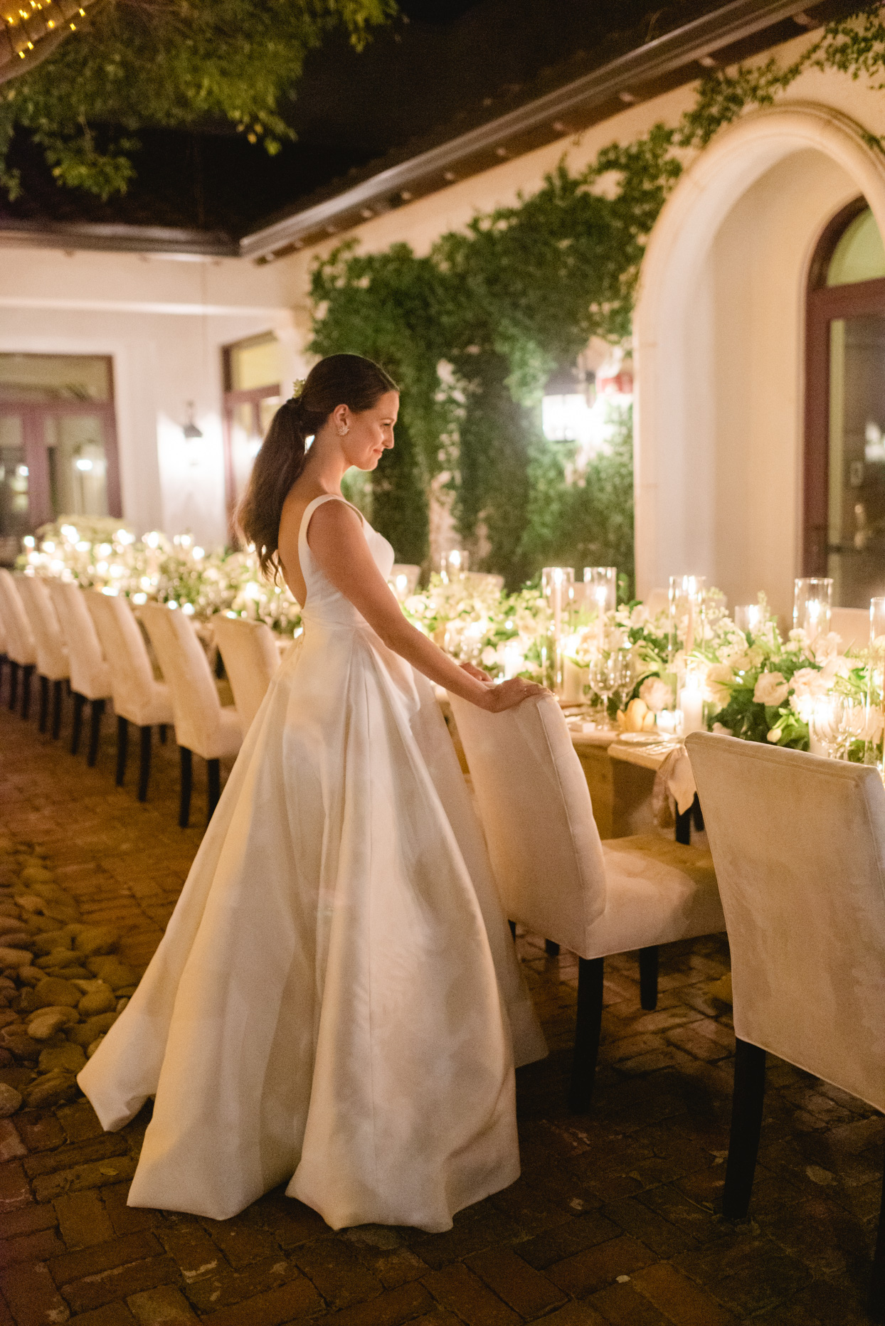 bride standing at empty reception tables lit with candles