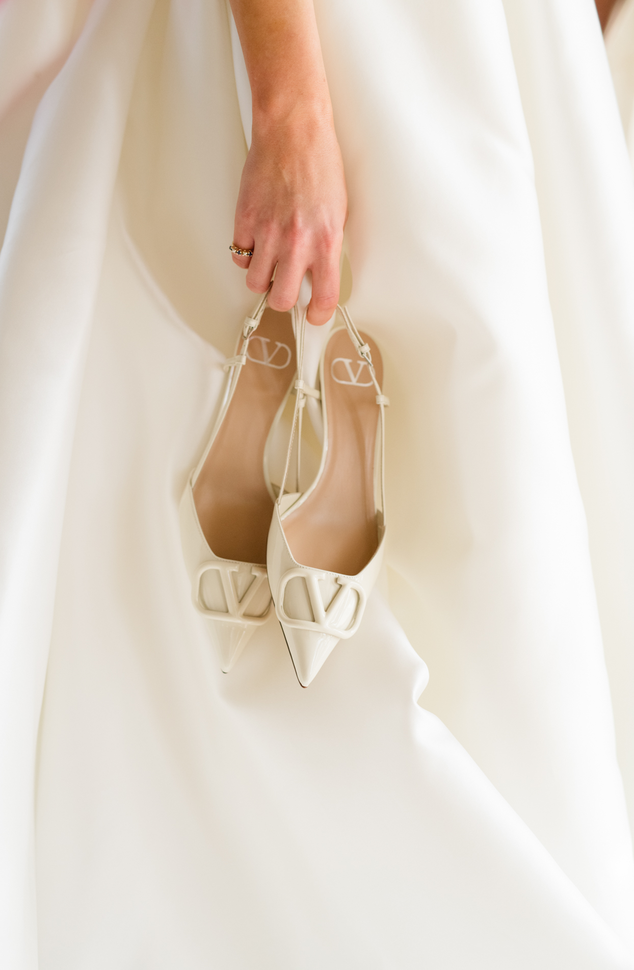 bride carrying white wedding shoes