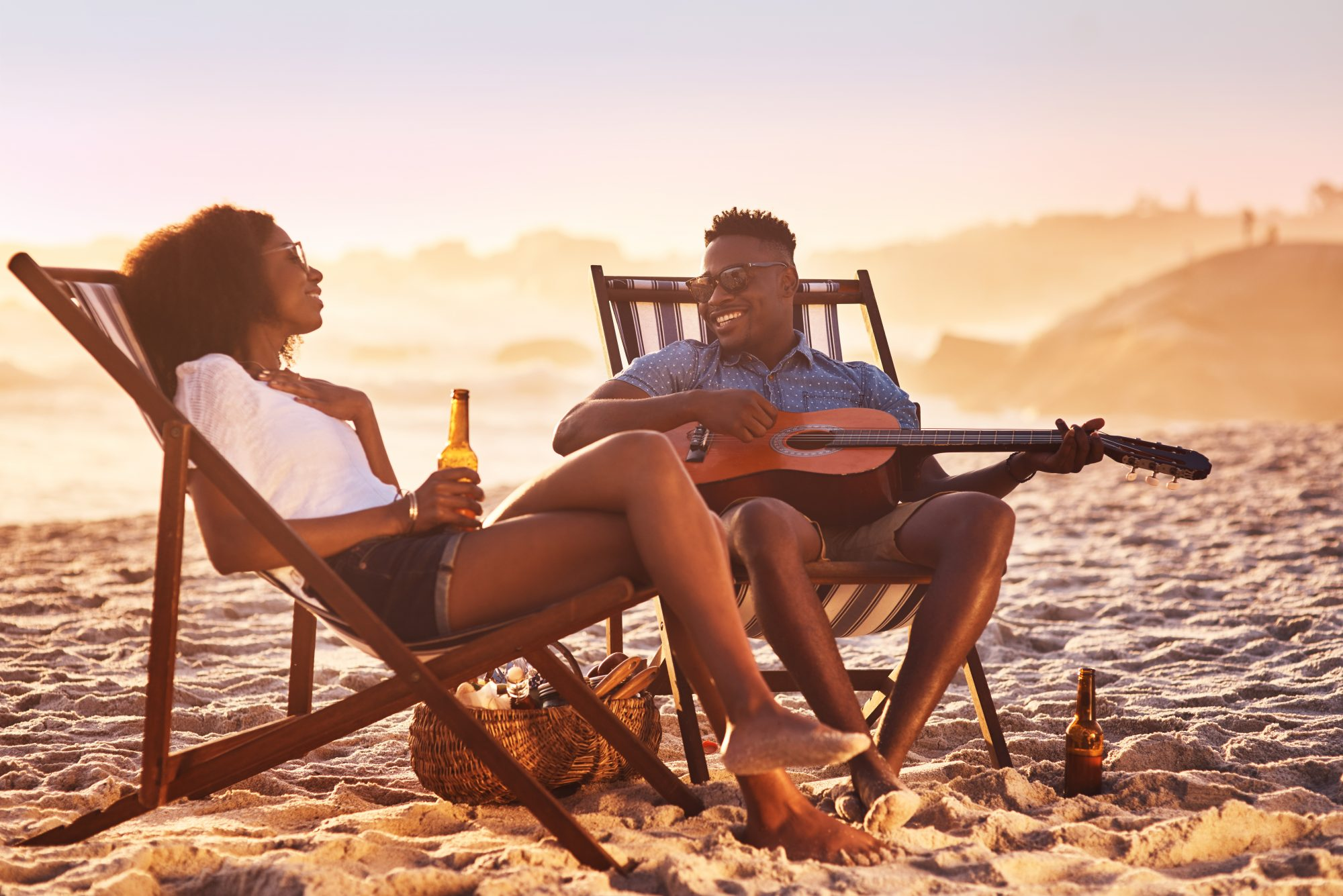 couple at beach sitting in chairs playing guitar