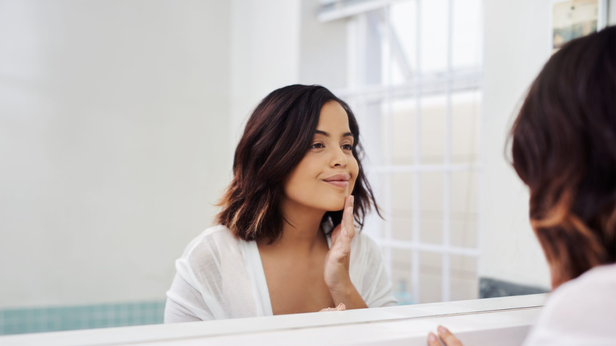 woman touching face looking in mirror