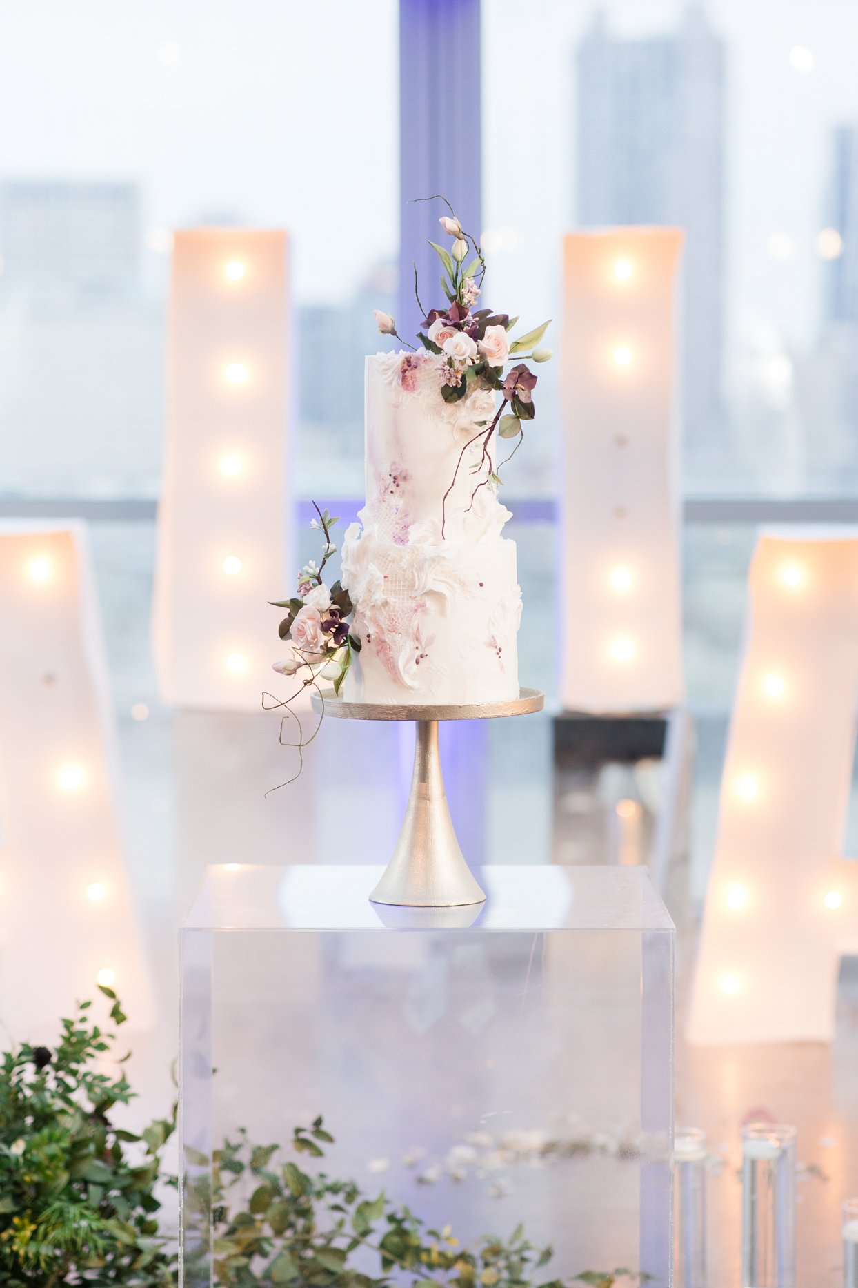 white wedding cake with pastel pink and purple accents