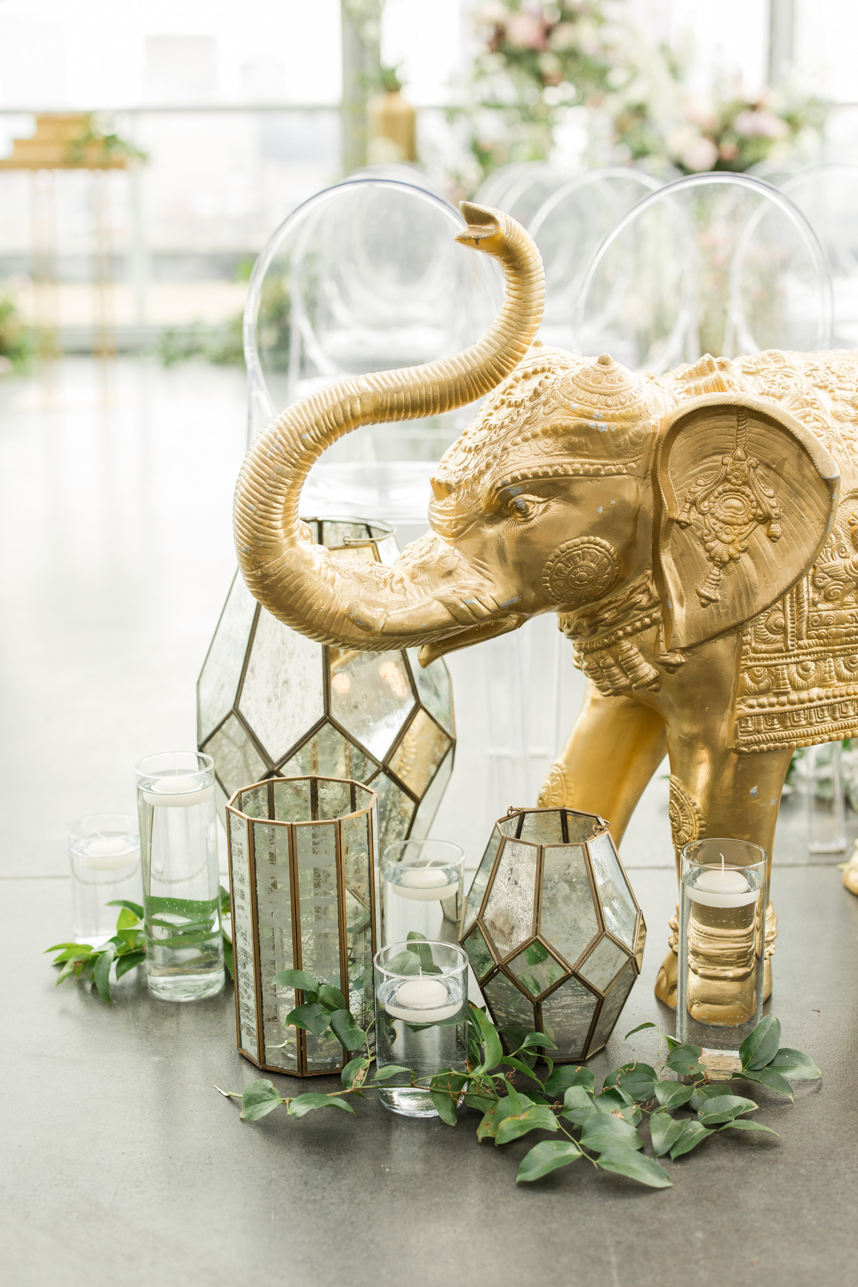 golden elephant and candle decor in wedding aisle
