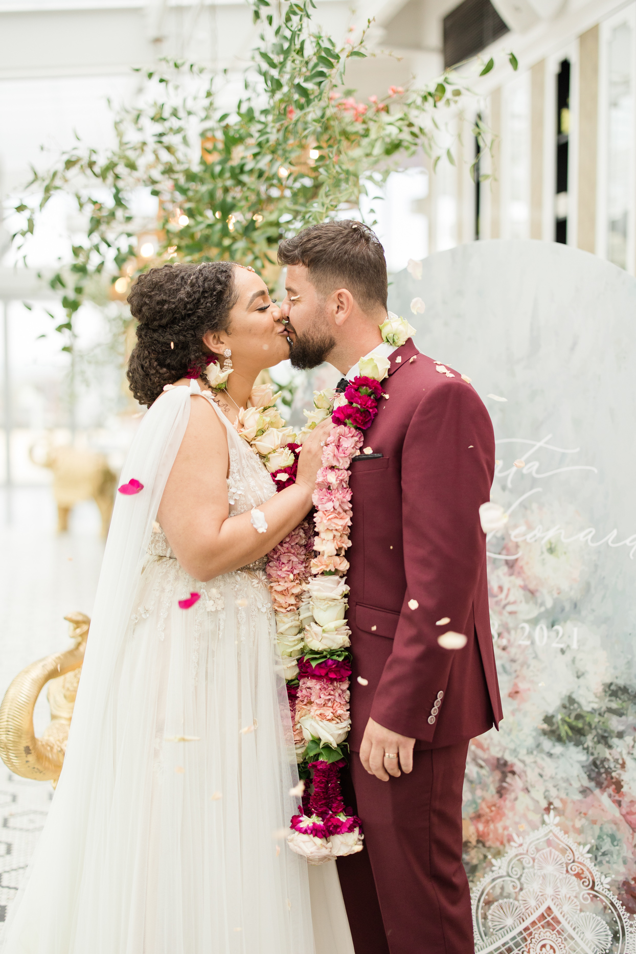 couple kissing at ceremony with being showered in flower petals