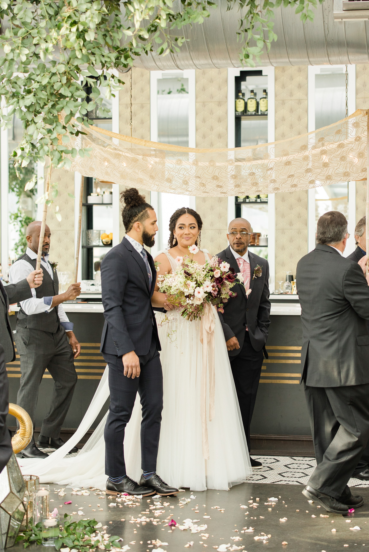 bride processing at wedding ceremony with men in suits